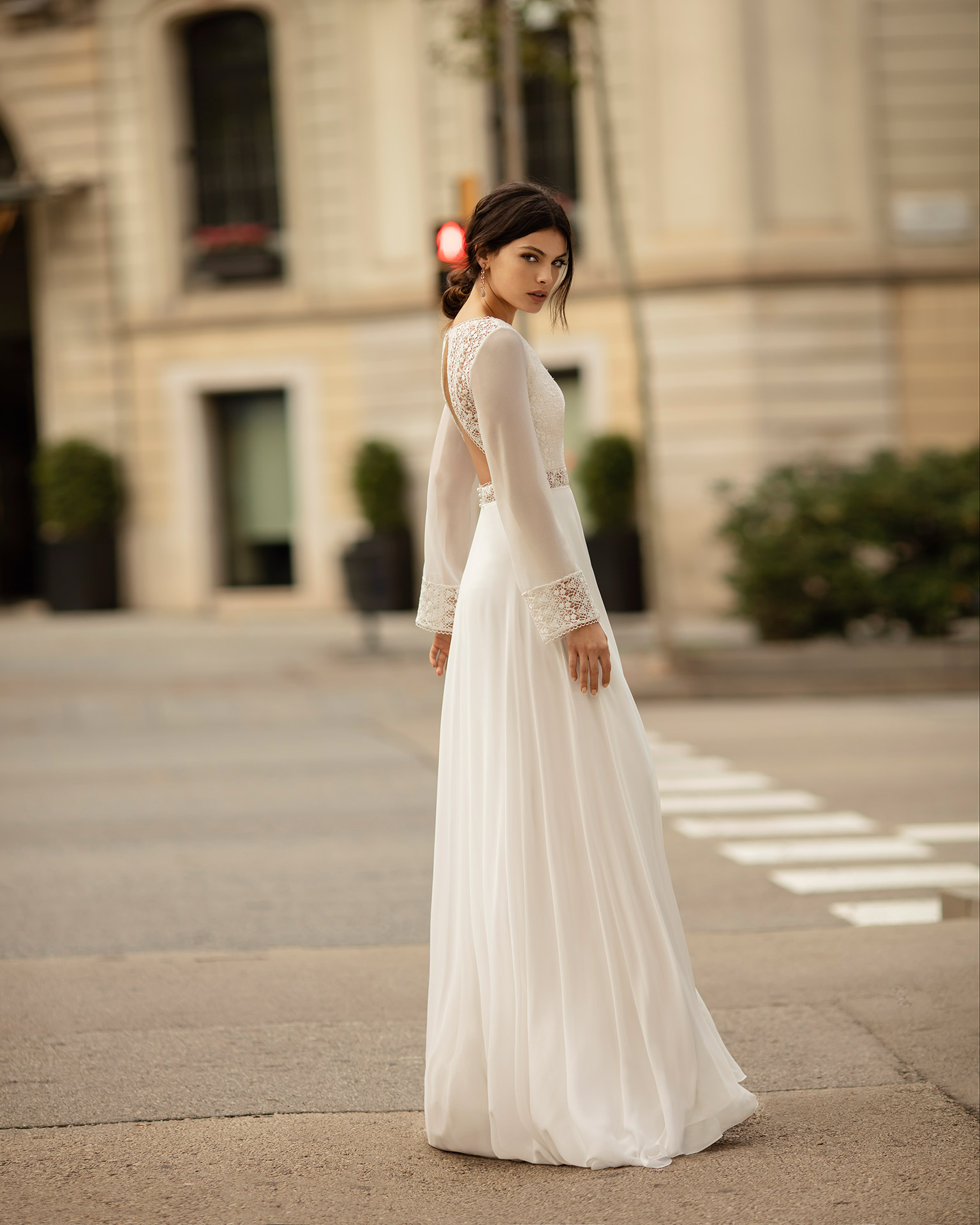 Boho-style lace and chiffon wedding dress with deep-plunge neckline, low back and long sleeves. 2020 ALMA_NOVIA Collection.