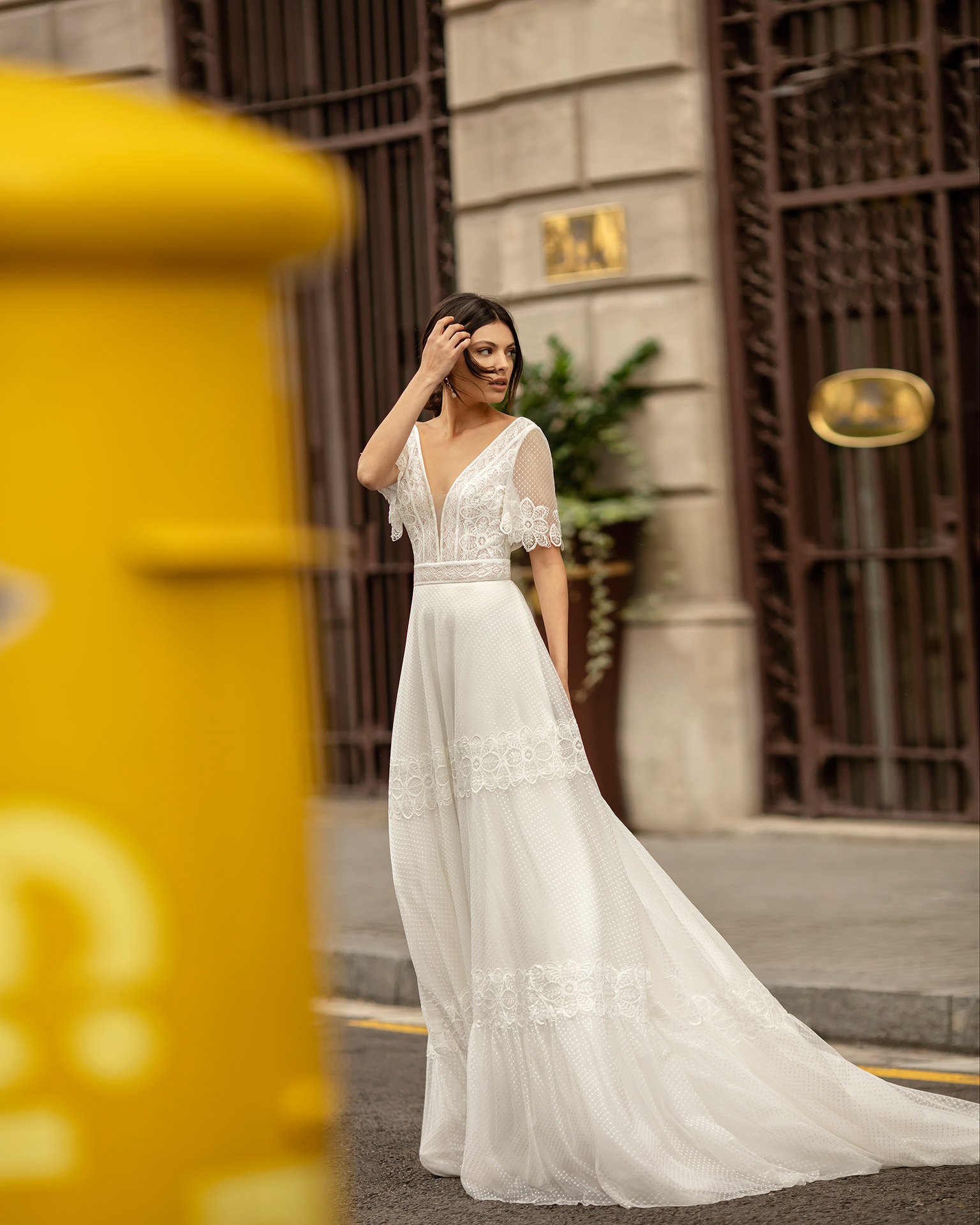 Boho-style lace and dot tulle wedding dress with deep-plunge neckline, V-back and short sleeves. 2020 ALMA_NOVIA Collection.