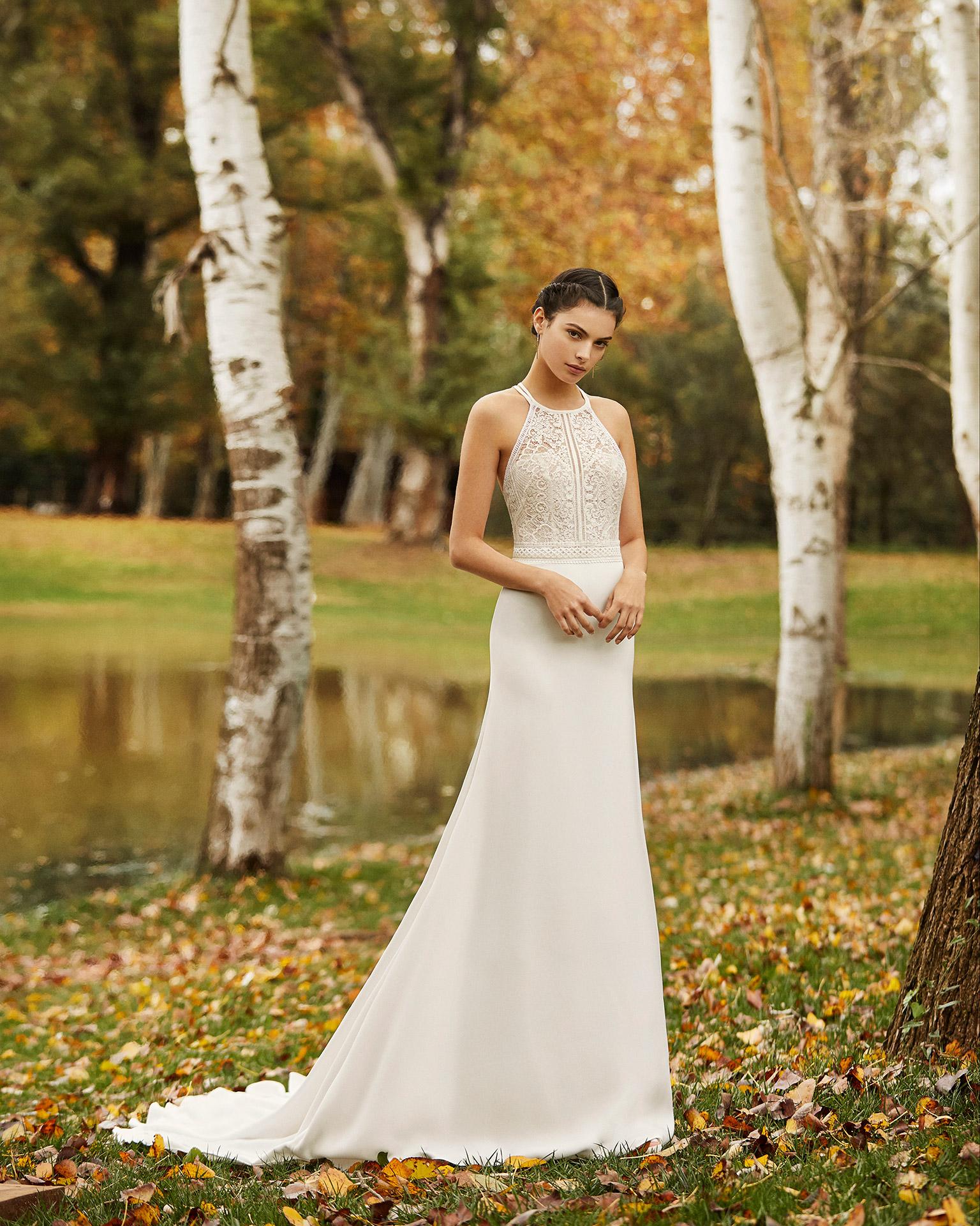 Vestido de novia estilo ligero crep y encaje pedrería con cuello halter y espalda de tirantes cruzados. Colección ALMANOVIA 2020.
