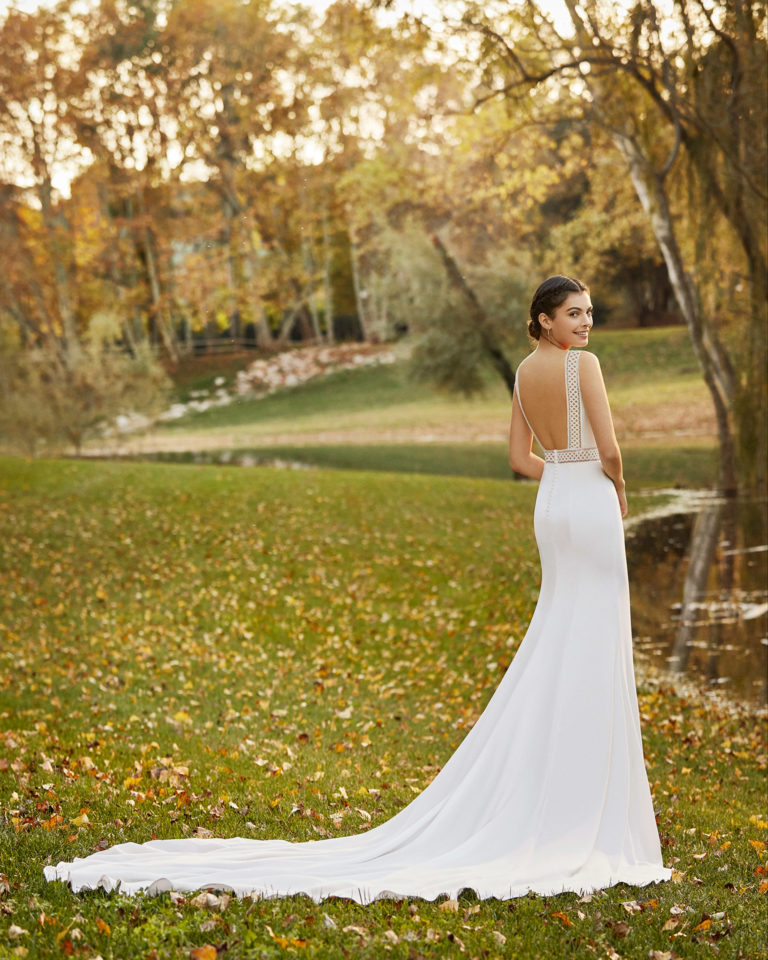Elegant lace and crepe wedding dress with bateau neckline and low back. 2020 ALMA_NOVIA Collection.