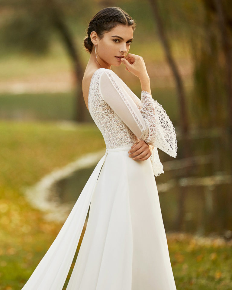 Boho-style lace and chiffon wedding dress and train with deep-plunge neckline, V-back and three-quarter sleeves with flounces. 2020 ALMANOVIA Collection.