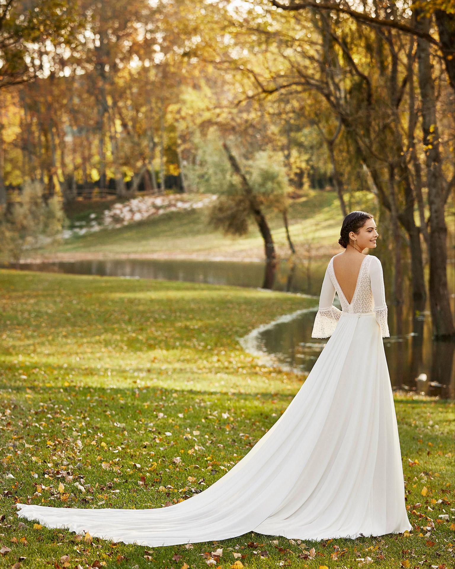 Vestido y cola de novia estilo boho de gasa y encaje, con escote deep-plunge y espalda en V con manga 3/4 con volante. Colección ALMANOVIA 2020.