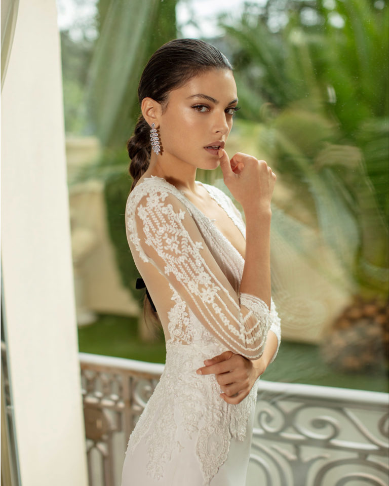 Lightweight chiffon and lace wedding dress with beading, deep-plunge neckline, back with sheer inserts and three-quarter sleeves. 2020 ALMANOVIA Collection.