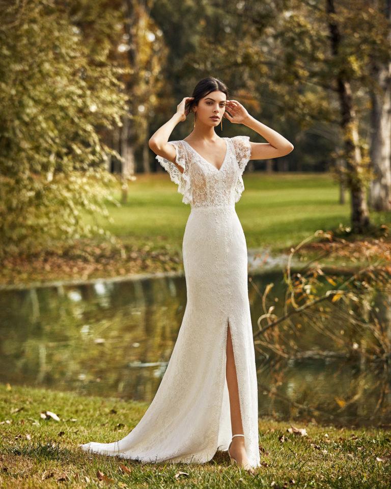 Vestido de novia estilo boho de encaje y pedrería con abertura delantera, con escote en V y espalda cerrada con manga volantes. Colección ALMA_NOVIA 2020.