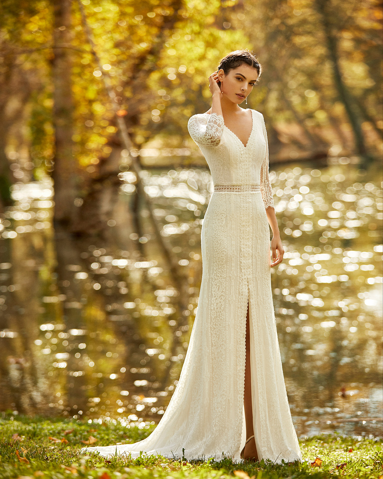 Boho-style lace wedding dress with front slit, V-neckline and closed back with three-quarter sleeves. 2020 ALMA_NOVIA Collection.