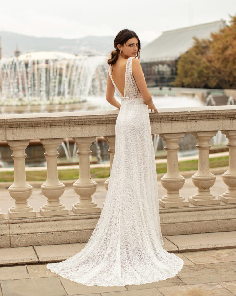 Boho-style lace wedding dress with deep-plunge neckline and V-back. 2020 ALMA_NOVIA Collection.