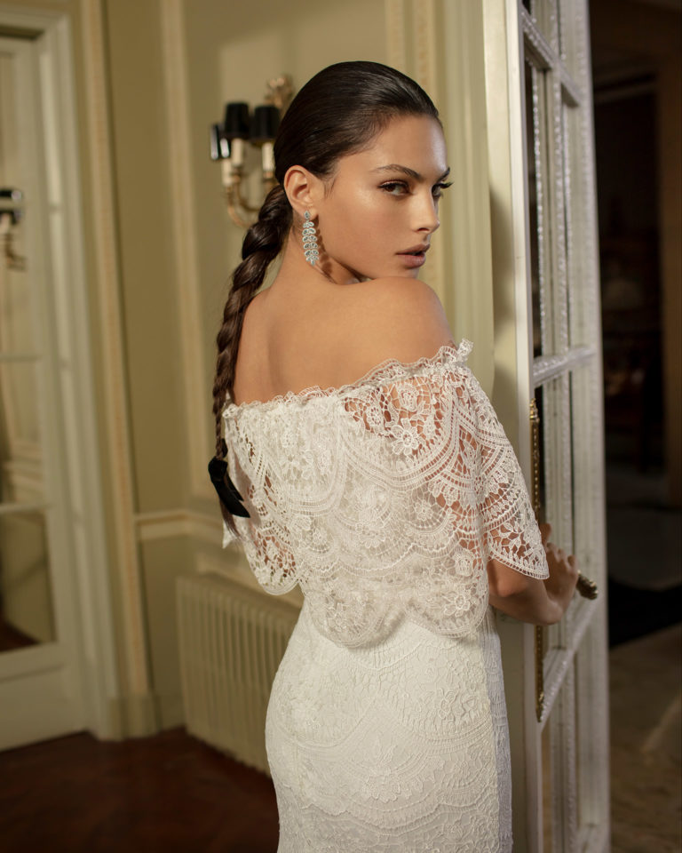 Boho-style lace wedding dress with off-the-shoulder neckline and flounces. 2020 ALMANOVIA Collection.