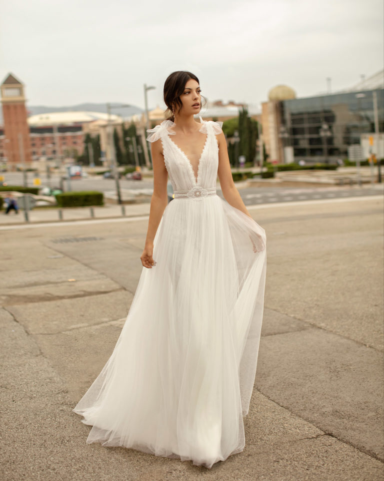 Romantic wedding dress and watteau train in soft tulle and lace with beading, with deep-plunge neckline. 2020 ALMANOVIA Collection.