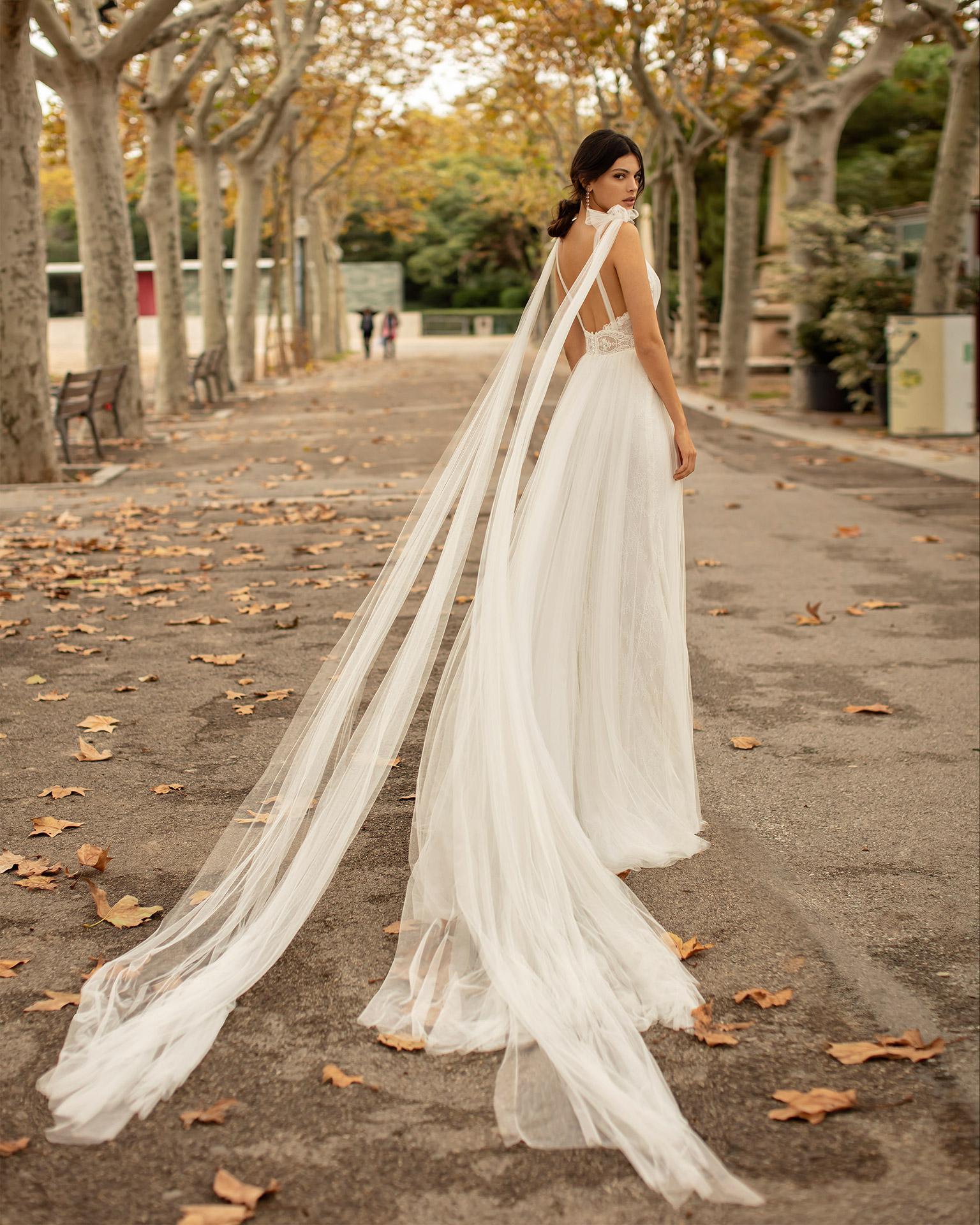 Vestido y caídas de novia estilo romántico de tul suave, encaje y pedrería con escote deep-plunge. Colección ALMANOVIA 2020.