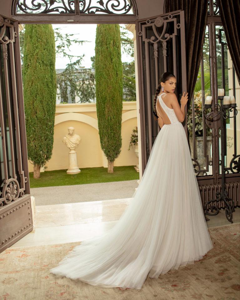 Vestido de novia estilo romántico de tul suave, encaje y pedrería con espalda escotada. Colección ALMANOVIA 2020.