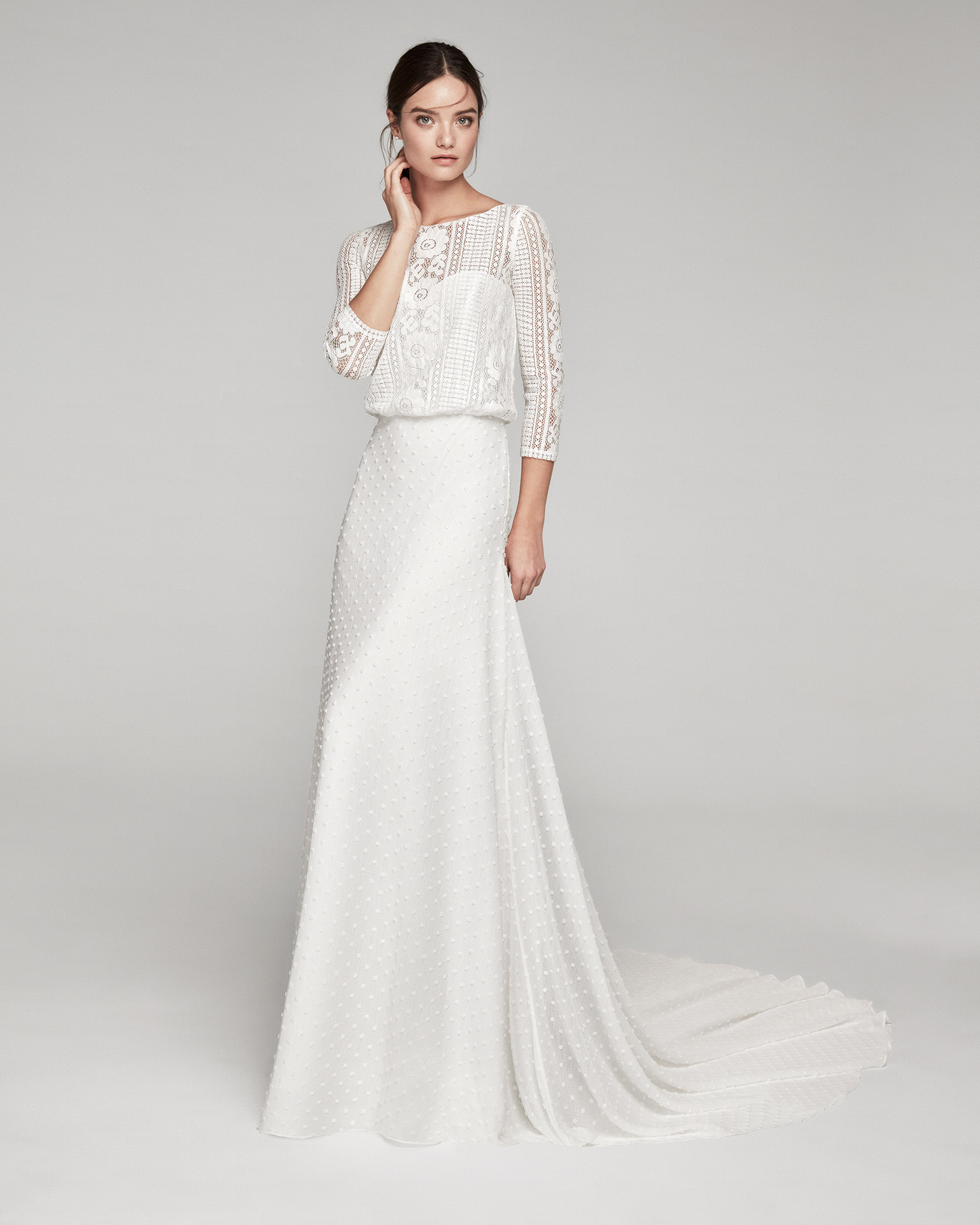 Boho-style wedding dress in lace. Bateau neckline with three-quarter sleeves and polka-dot gauze skirt. Available in natural. 2020 ALMANOVIA Collection.