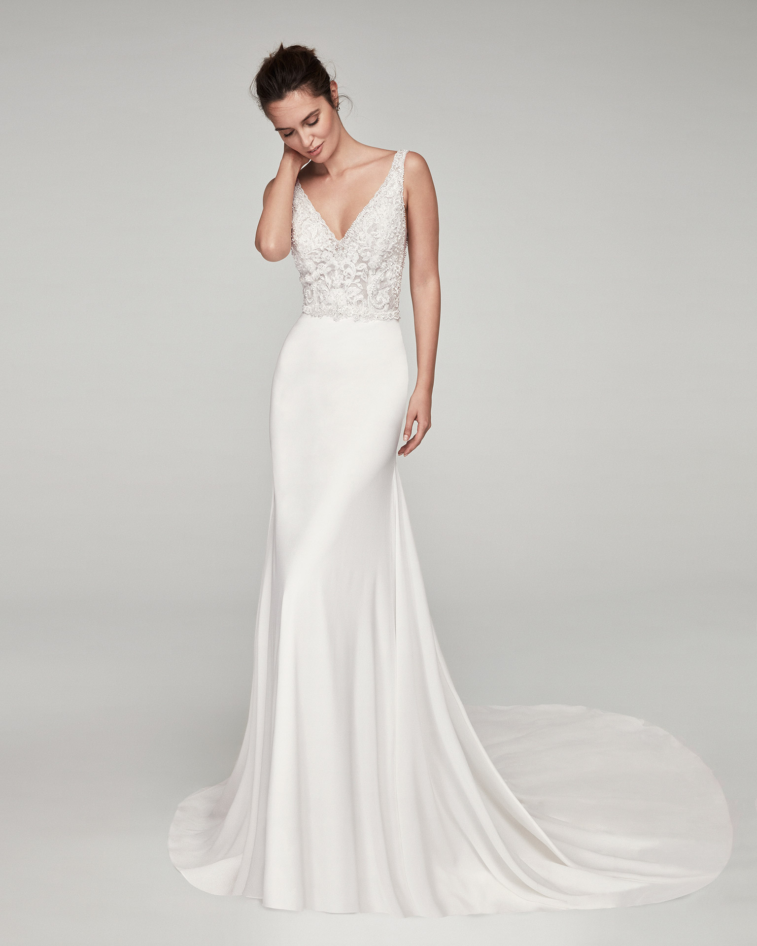Sheath-style wedding dress in crepe Georgette and beaded lace. With V-neckline and back. Available in natural. 2020 ALMANOVIA Collection.