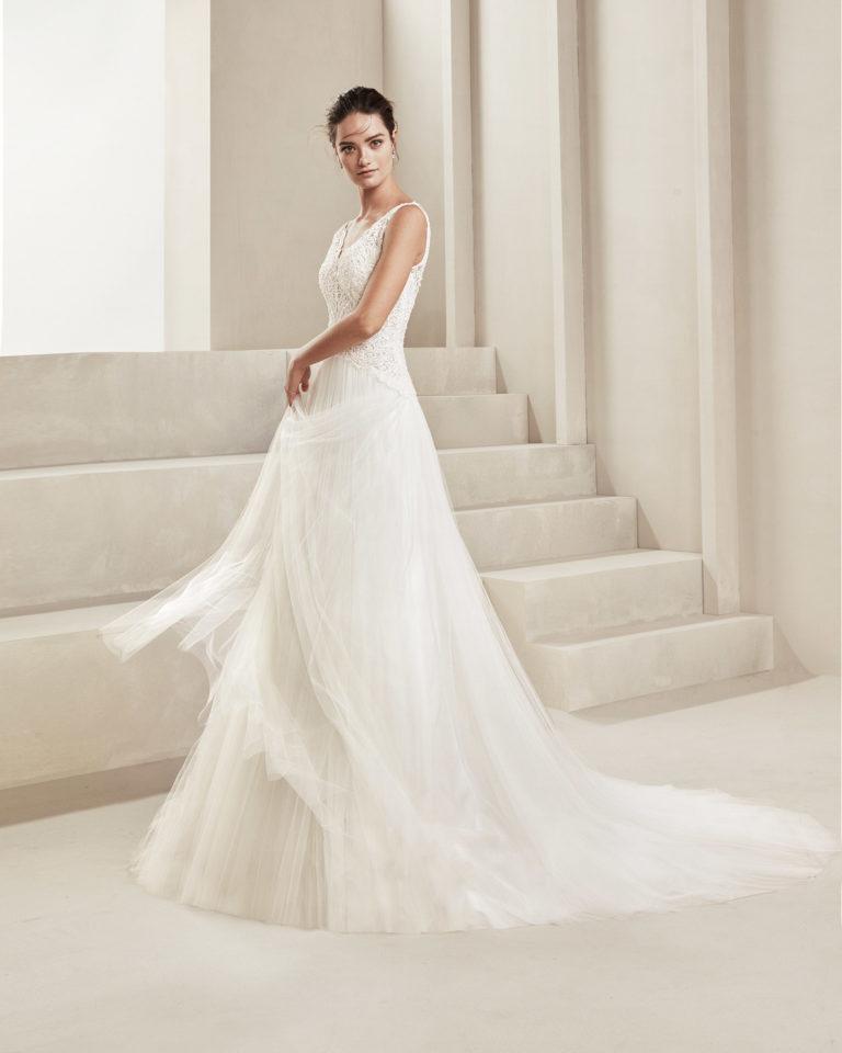 Vestido de novia romántico de tul suave, encaje y pedrería. Con escote V y espalda en tul. Disponible en color natural. Colección ALMANOVIA 2020.