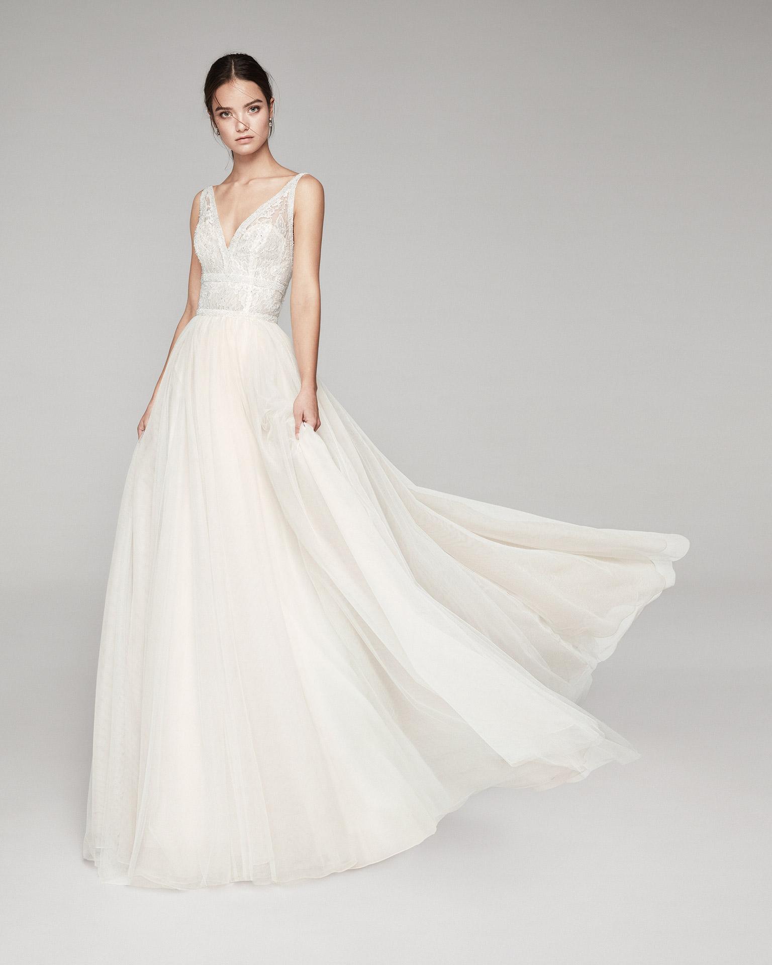 Vestido de novia romántico de tul suave, encaje y pedrería. Con escote V, espalda escotada con línea de pedrería. Disponible en color natural/nude y natural. Colección ALMANOVIA 2020.