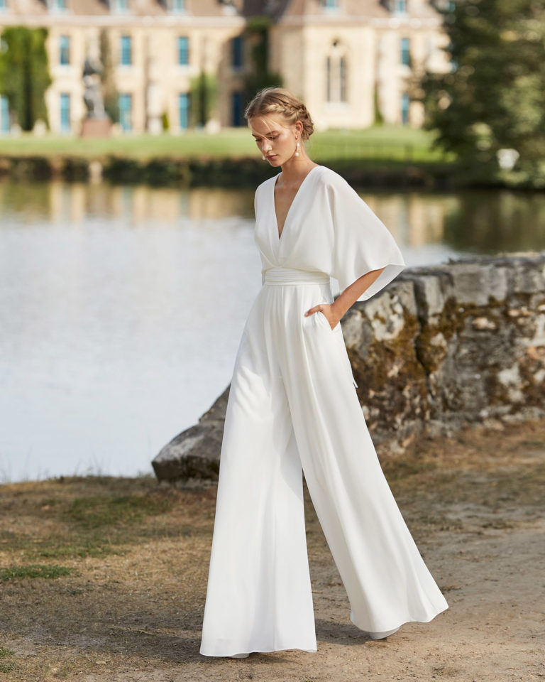 Bridal culotte jumpsuit suit in crepe. Bloused V-neckline, of-the-shoulder three-quarter sleeves and low back. 2021 ALMANOVIA Collection.