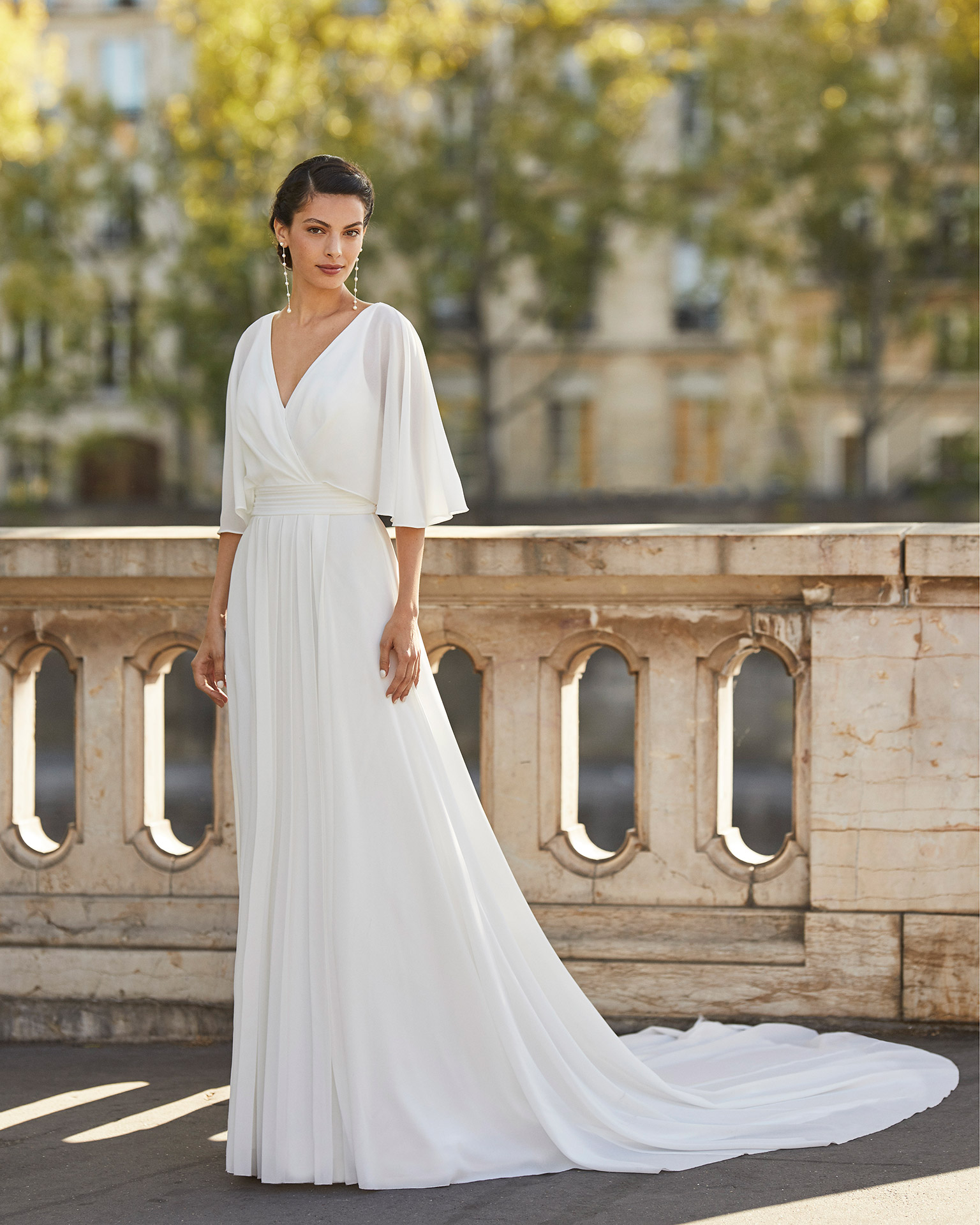 Wedding dress in stretch crepe Georgette. V-neckline, flared sleeves and low square back with bow braid. 2021 ALMANOVIA Collection.