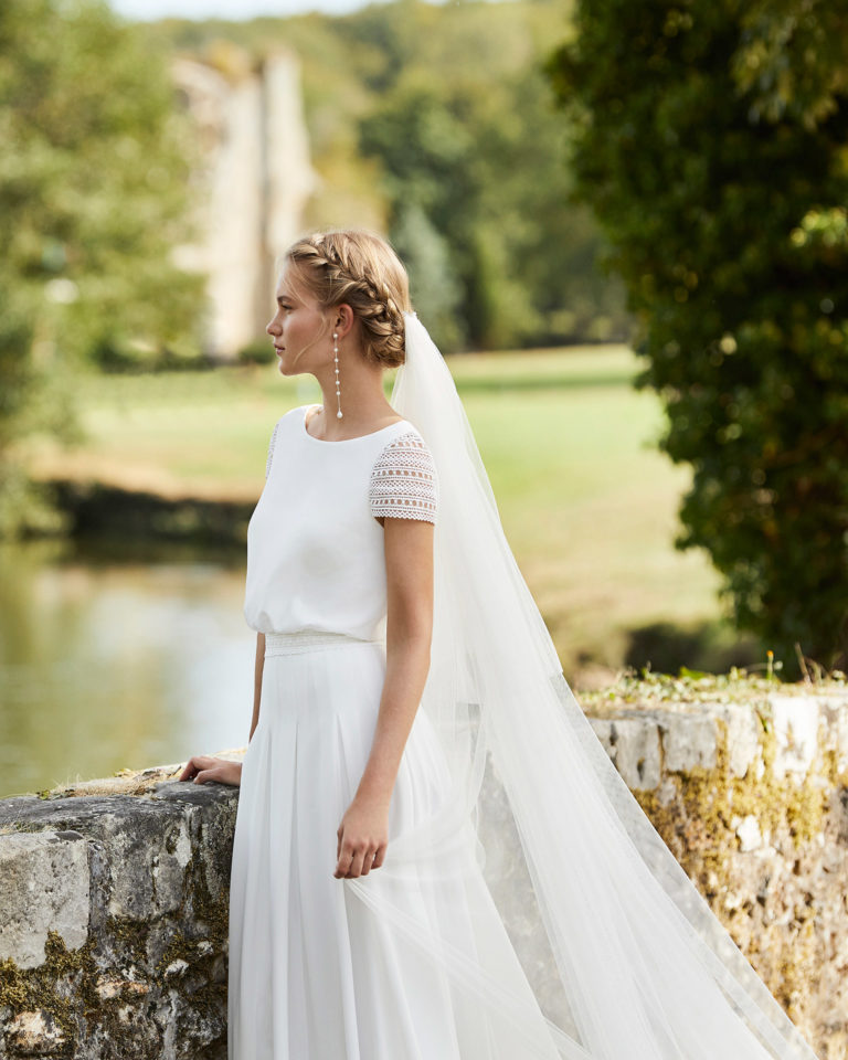 Wedding dress in stretch crepe Georgette. Bateau neckline, short lace sleeves and V-back. 2021 ALMANOVIA Collection.