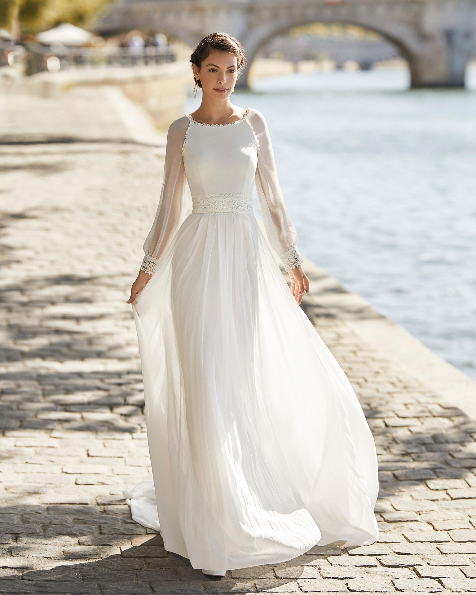 Vestido de novia de gasa. Escote barco, manga larga de gasa con puño de encaje y espalda cerrada. Colección ALMANOVIA 2021.