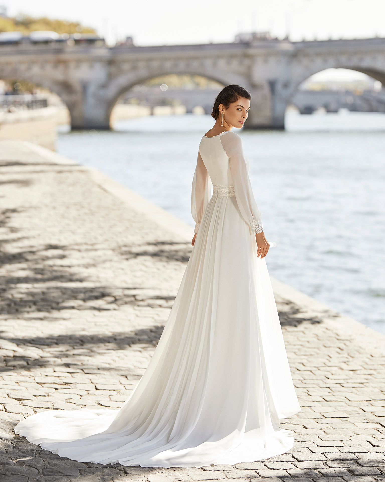 Wedding dress in chiffon. Bateau neckline, long sleeves in chiffon with lace cuff, and closed back. 2021 ALMANOVIA Collection.