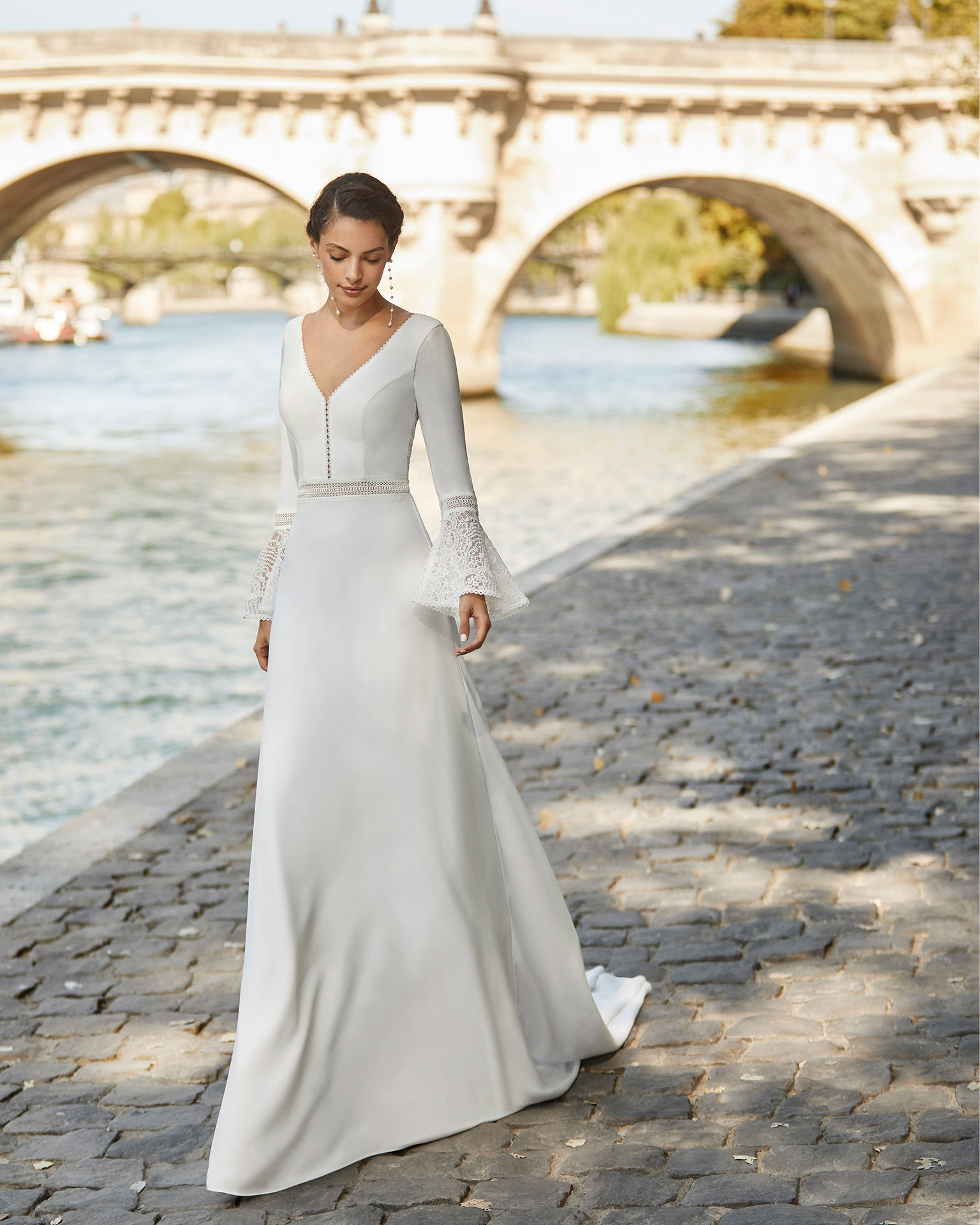 Wedding dress in crepe. V-neckline, long flared sleeves in crepe and lace, beaded lace belt and open V-back in lace. With shaper lining. 2021 ALMANOVIA Collection.