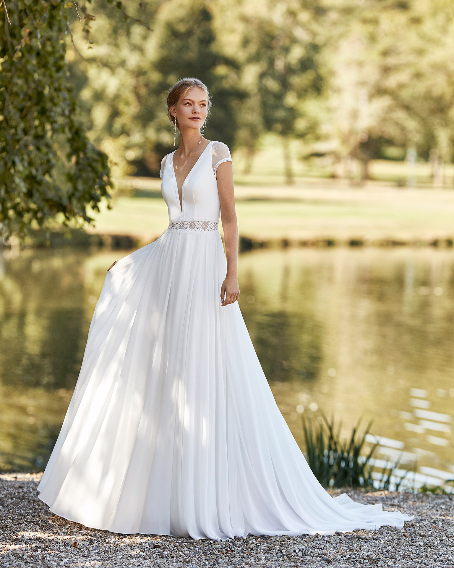 Wedding dress in chiffon. Deep-plunge V-neckline, short sleeves in dot tulle and lace and back in dot tulle with buttons. 2021 ALMANOVIA Collection.