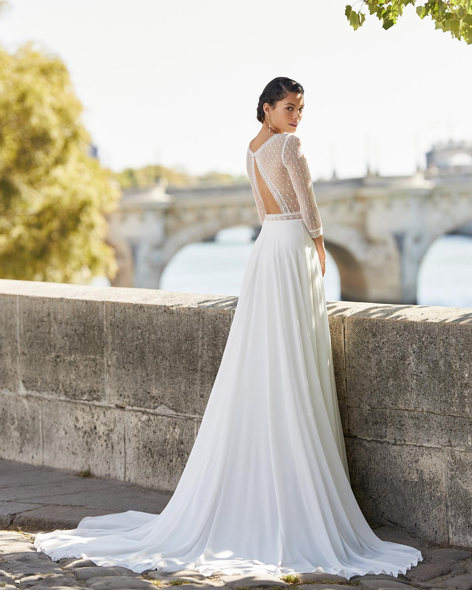 Vestido de novia de gasa. Escote en V, manga tres cuarto de tul plumeti acabado en encaje, espalda con forma triángulo de tul plumeti. Colección ALMANOVIA 2021.