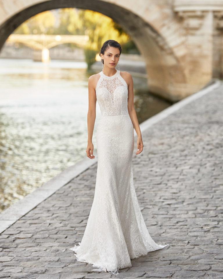 Vestido de novia de encaje. Escote halter con pedrería en cuello y sisas y espalda con tirantes atados en el cuello. Colección ALMANOVIA 2021.