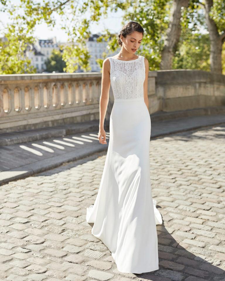 Wedding dress in crepe. Bateau neckline in lace, beaded lace belt, shoulder straps and V-back. 2021 ALMANOVIA Collection.