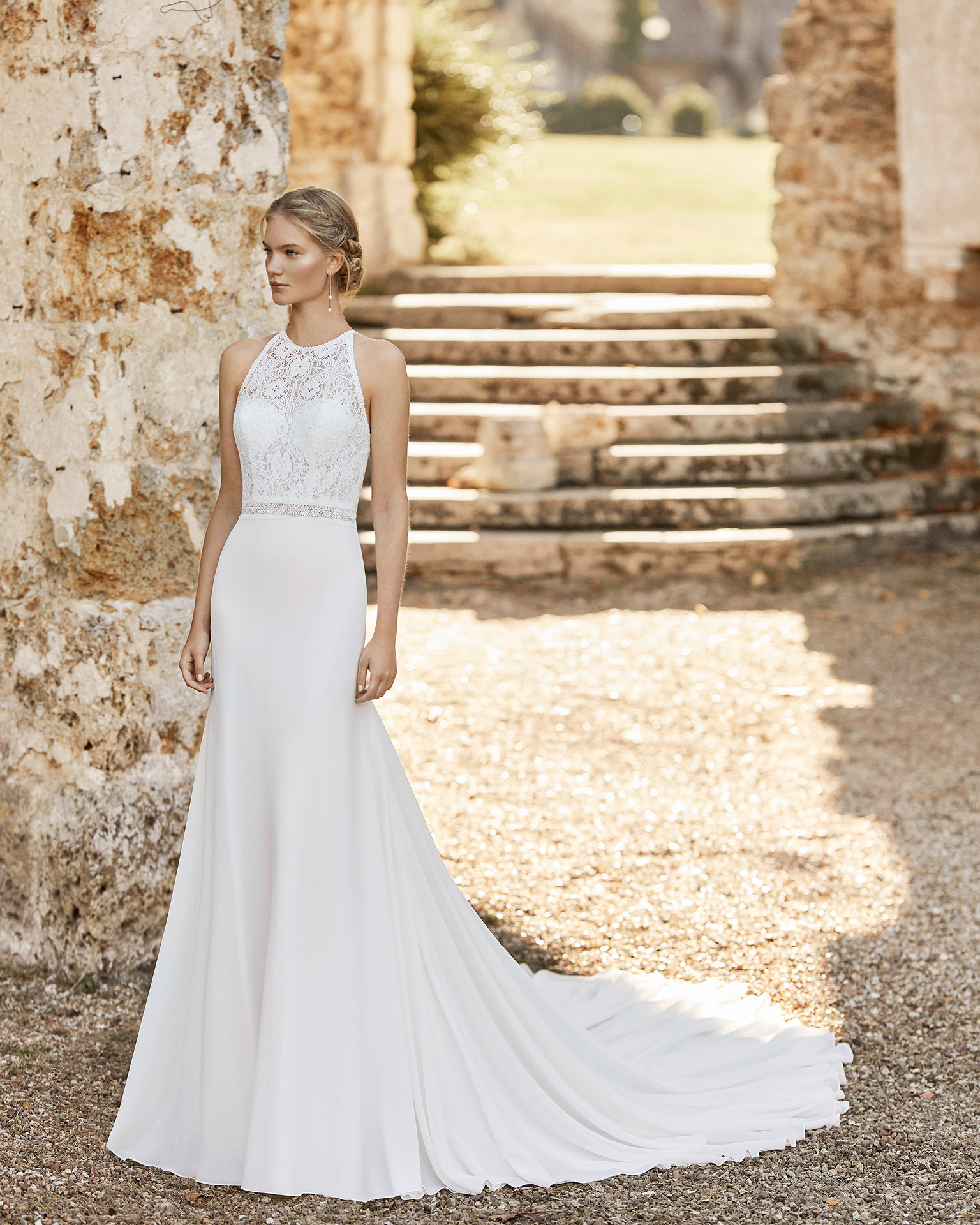 Wedding dress in chiffon. Halter neckline in lace, lace belt and open back with shoulder straps attached to collar. 2021 ALMANOVIA Collection.