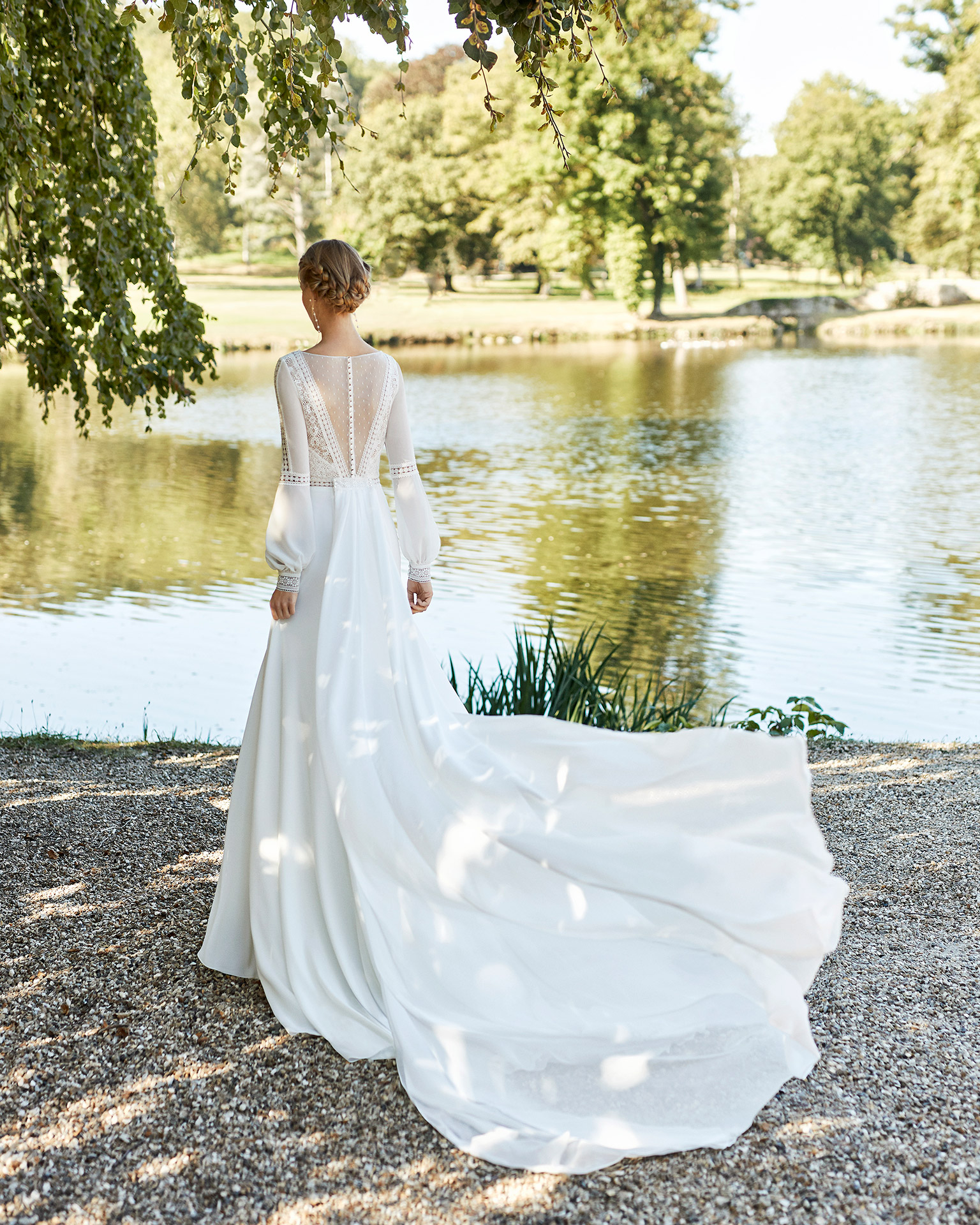 Wedding dress and train in crepe Georgette. V-neckline in lace, long puffed sleeves in crepe Georgette and back in dot tulle with buttons. 2021 ALMANOVIA Collection.