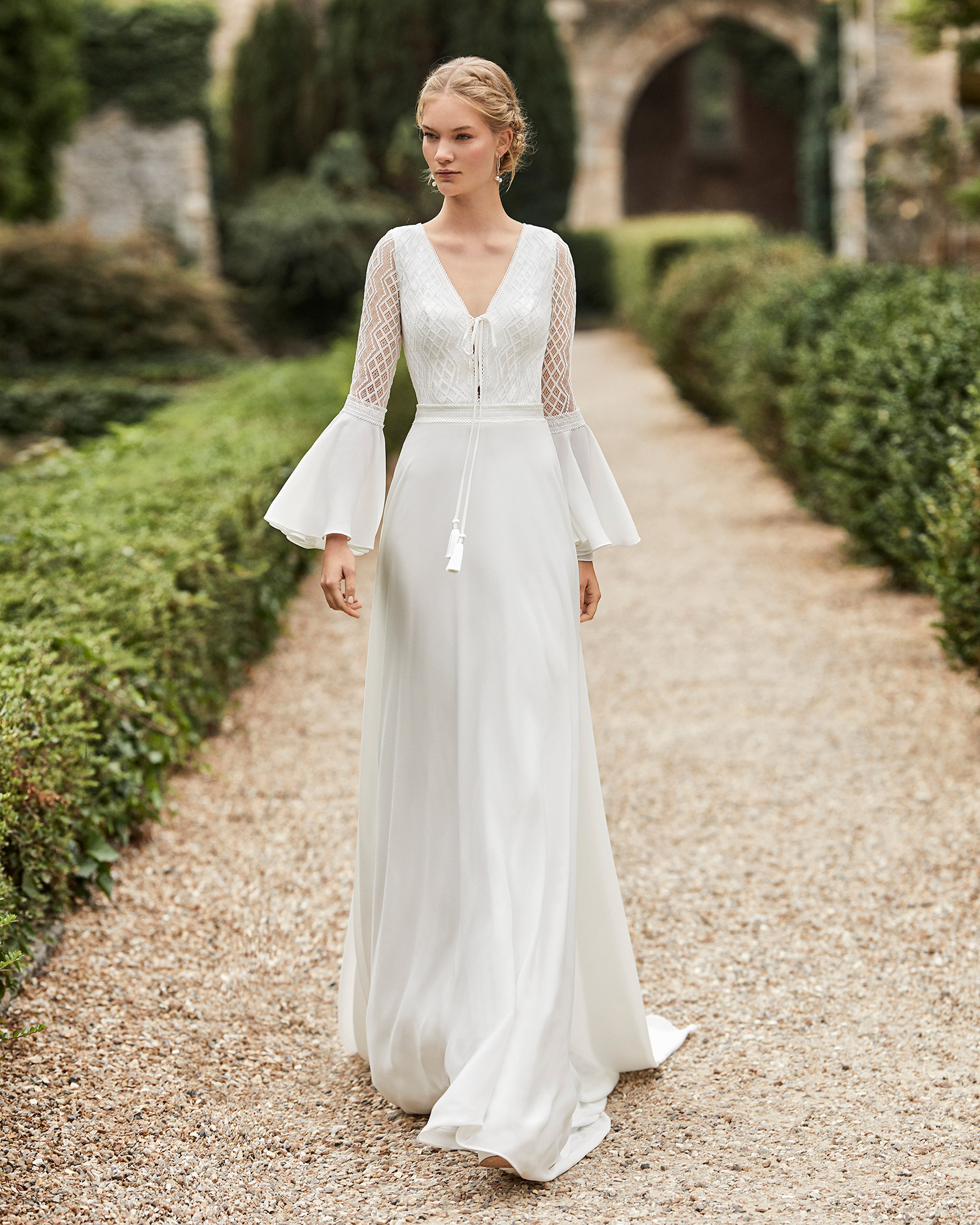 Wedding dress in crepe. V-neckline in lace, braid bow, long flared sleeves in lace and chiffon, lace belt and open teardrop back in lace. 2021 ALMANOVIA Collection.