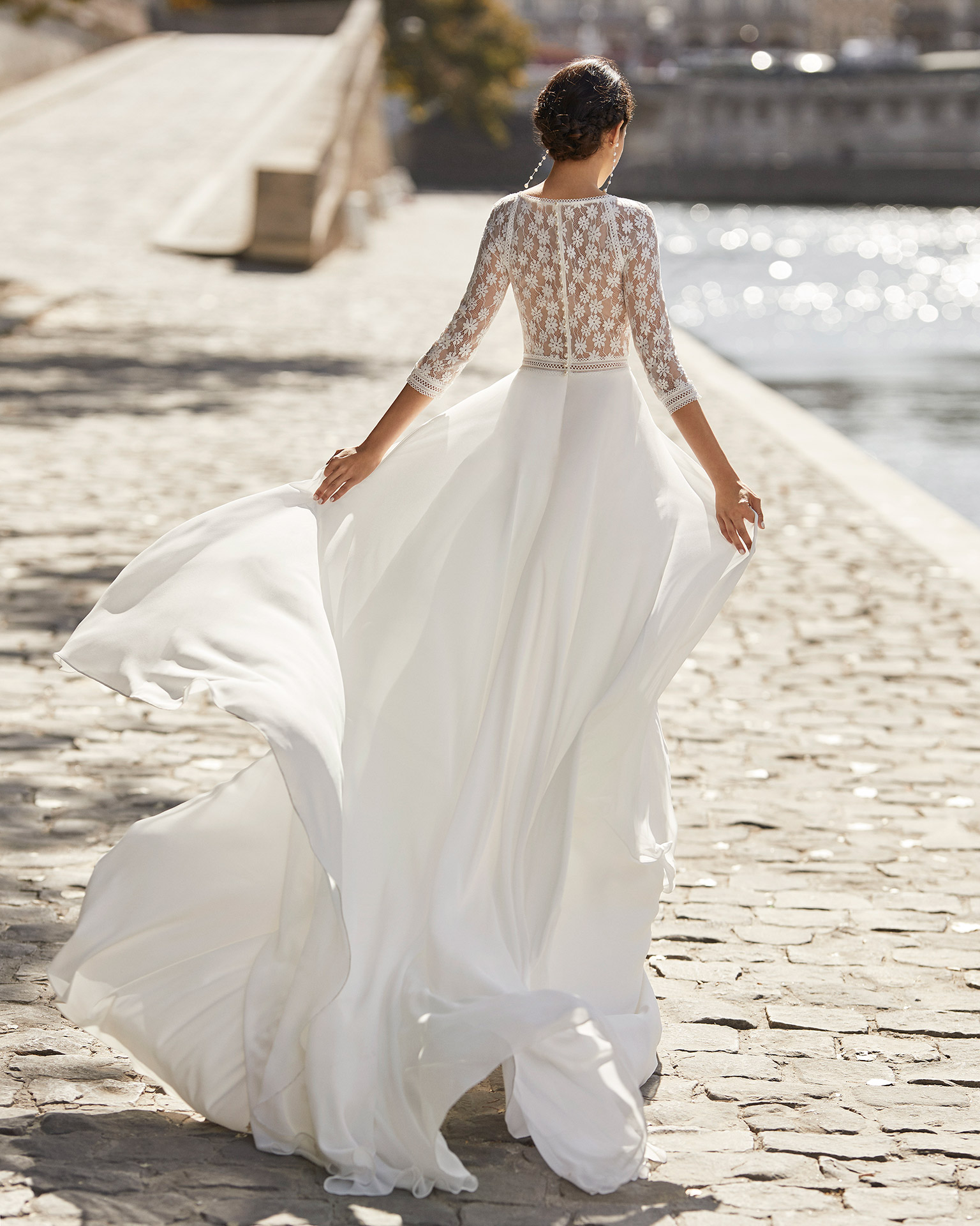 Wedding dress in chiffon. Closed neckline in lace, three-quarter sleeves in lace and lace back with buttons. 2021 ALMANOVIA Collection.
