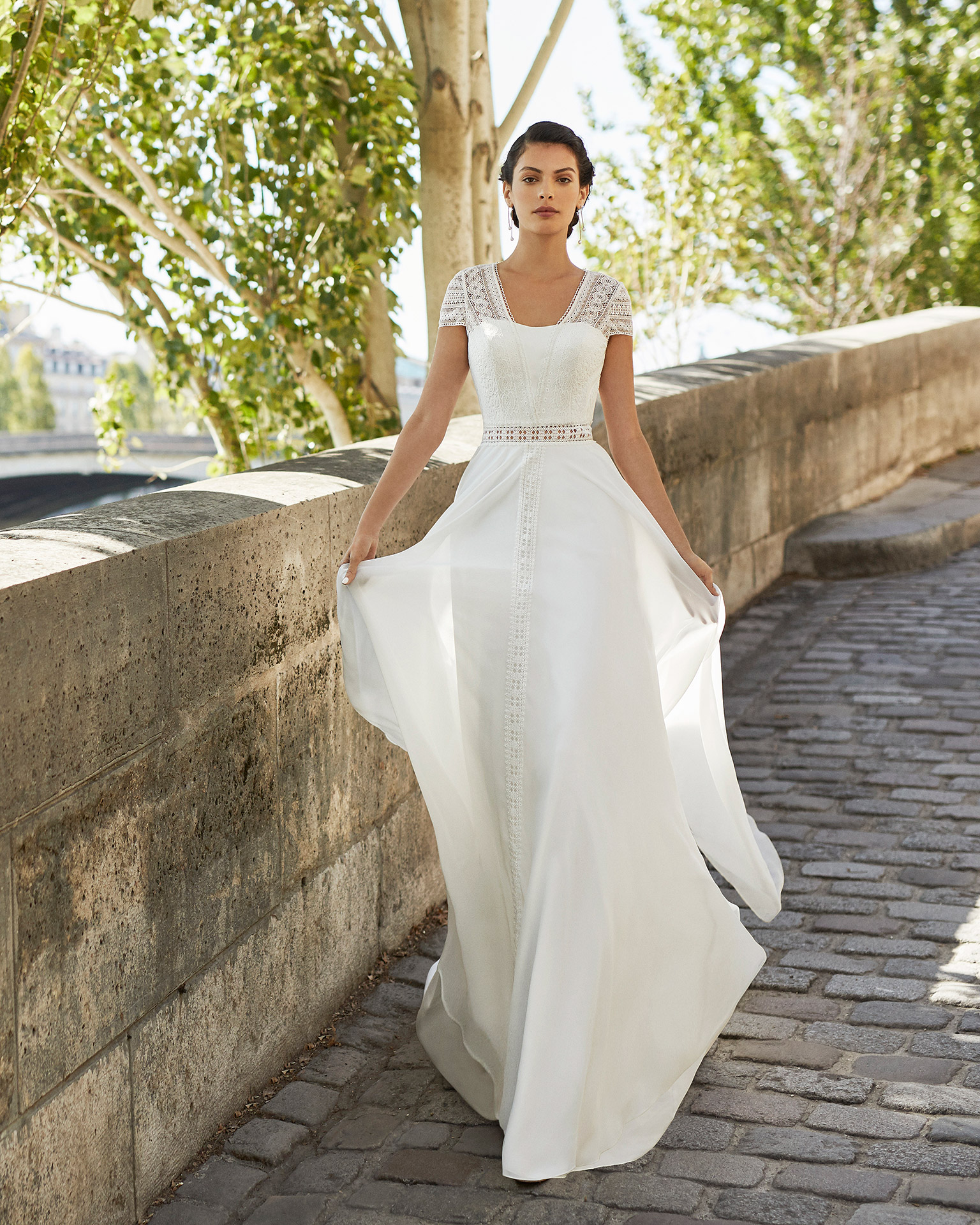 Wedding dress in chiffon. Strapless neckline with short lace sleeves and triangle back in lace. 2021 ALMANOVIA Collection.