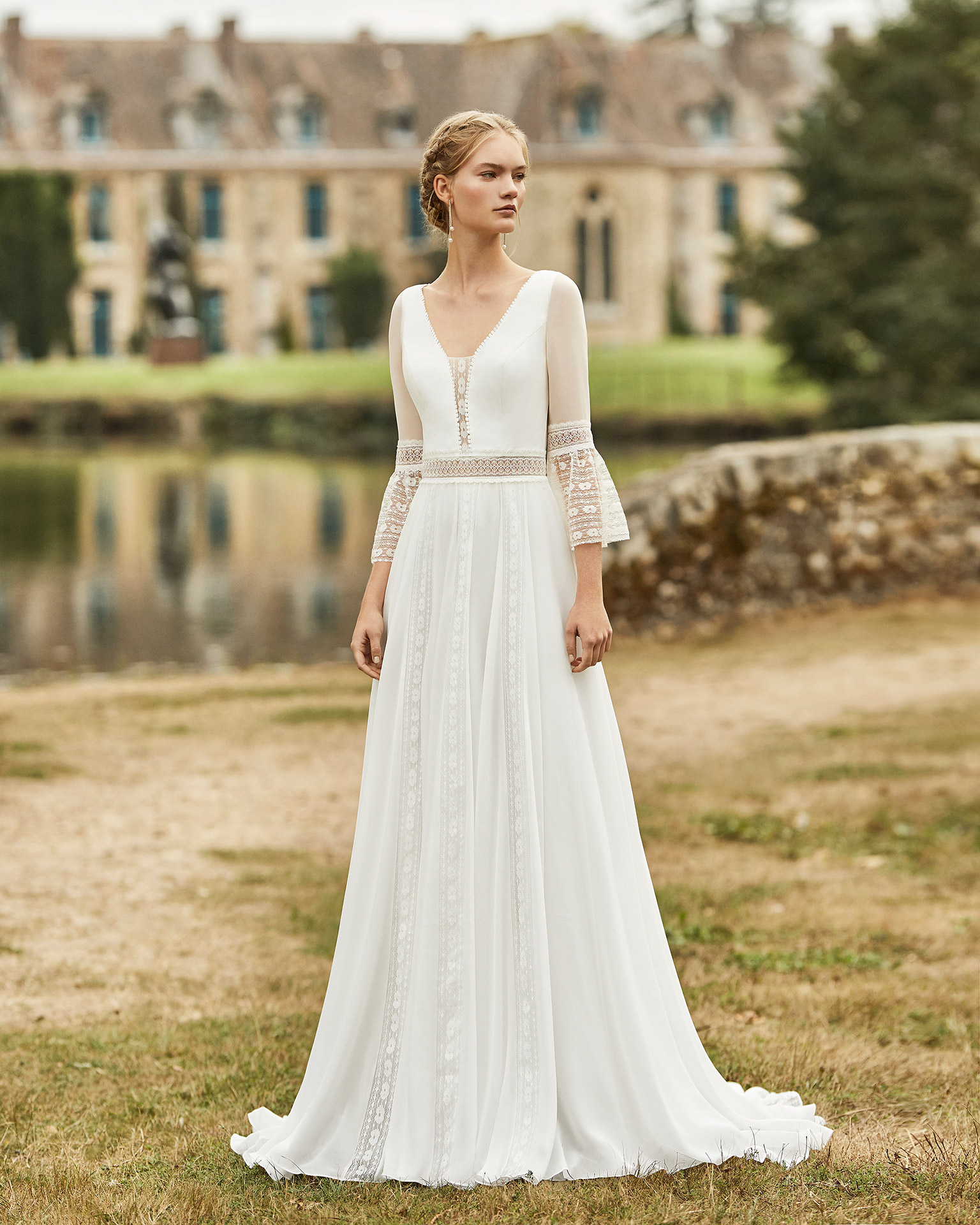Wedding dress in chiffon. Deep-plunge V-neckline, three-quarter sleeves in chiffon with flared lace cuffs, lace belt and open V-back in lace with braid bow. 2021 ALMANOVIA Collection.