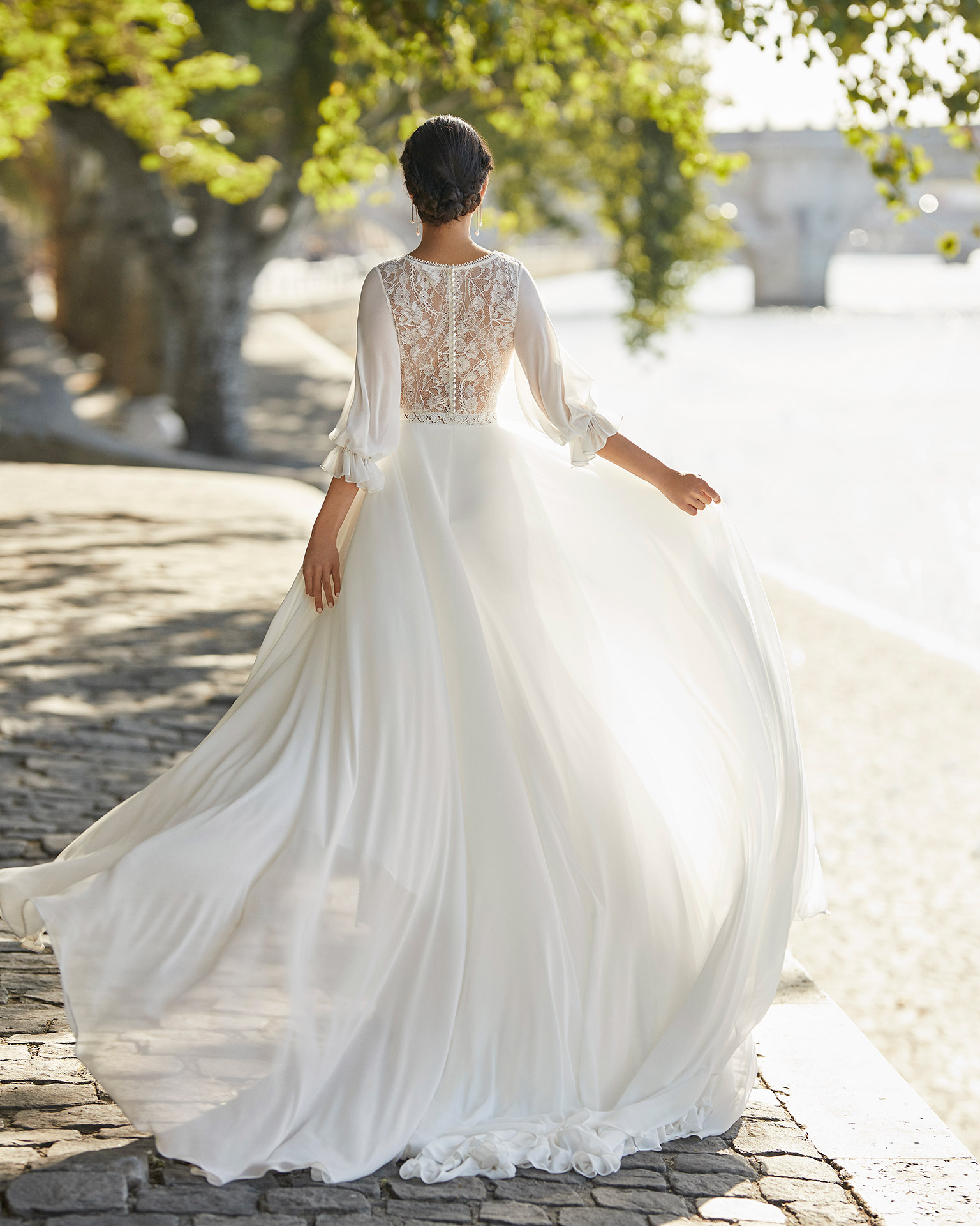 Wedding dress in chiffon. V-neckline in lace, bloused three-quarter sleeves in lace and closed back in lace with buttons. 2021 ALMANOVIA Collection.