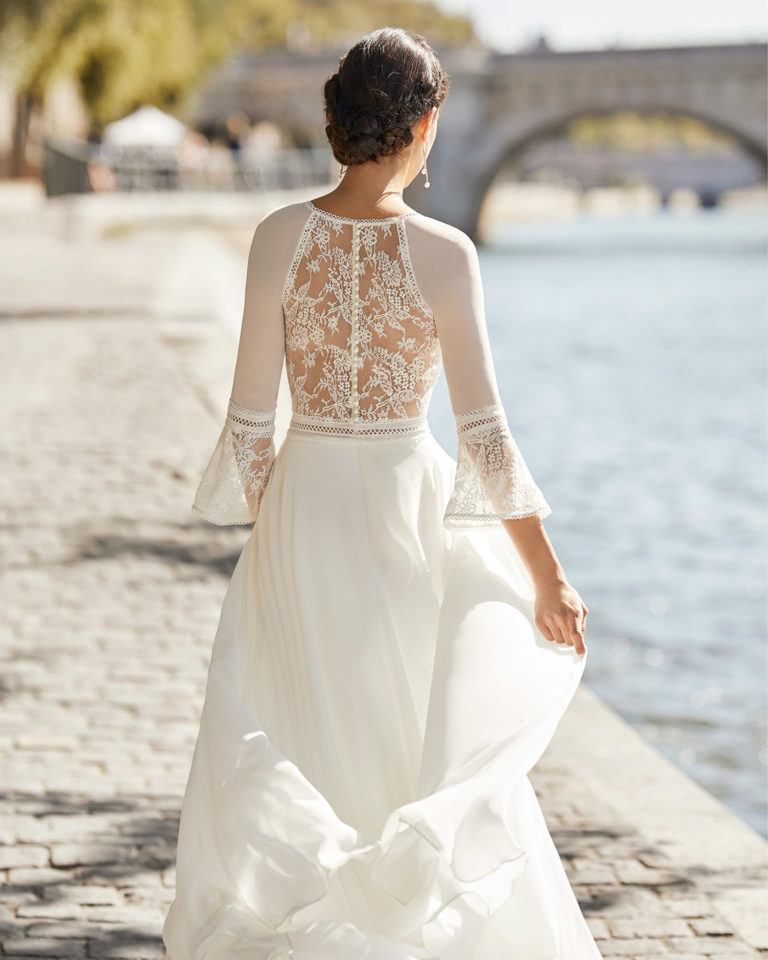Wedding dress in chiffon. V-neckline in lace, three-quarter sleeves in chiffon with flared lace cuffs and closed back in lace with buttons. 2021 ALMANOVIA Collection.