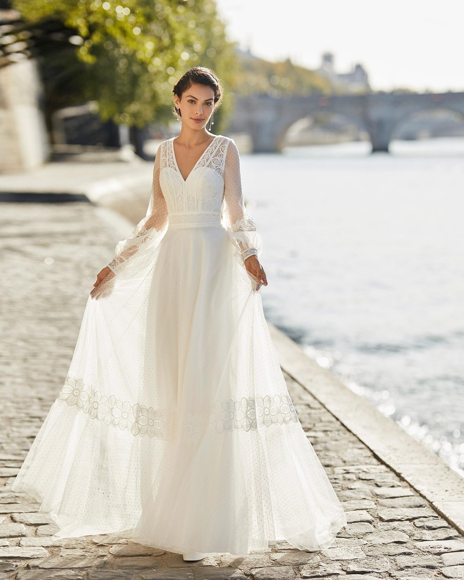 Vestido de novia de tul plumeti. Escote en V, manga larga de tul plumeti y espalda en forma de triángulo. Todo además con encaje. Colección ALMANOVIA 2021.