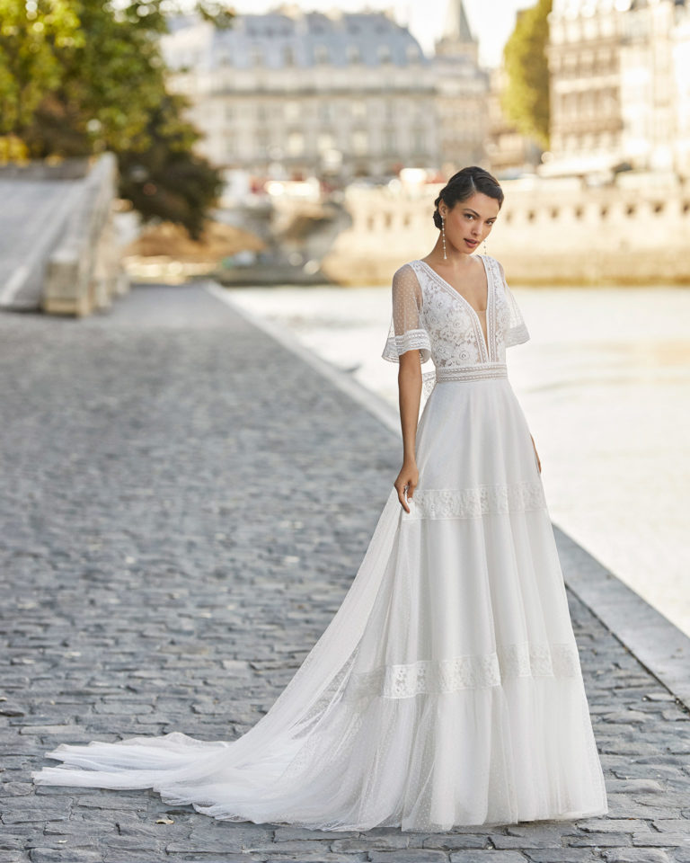 Wedding dress and train in dot tulle and lace. Deep-plunge V-neckline, short sleeves in dot tulle and lace, lace belt and V-back in lace. 2021 ALMANOVIA Collection.