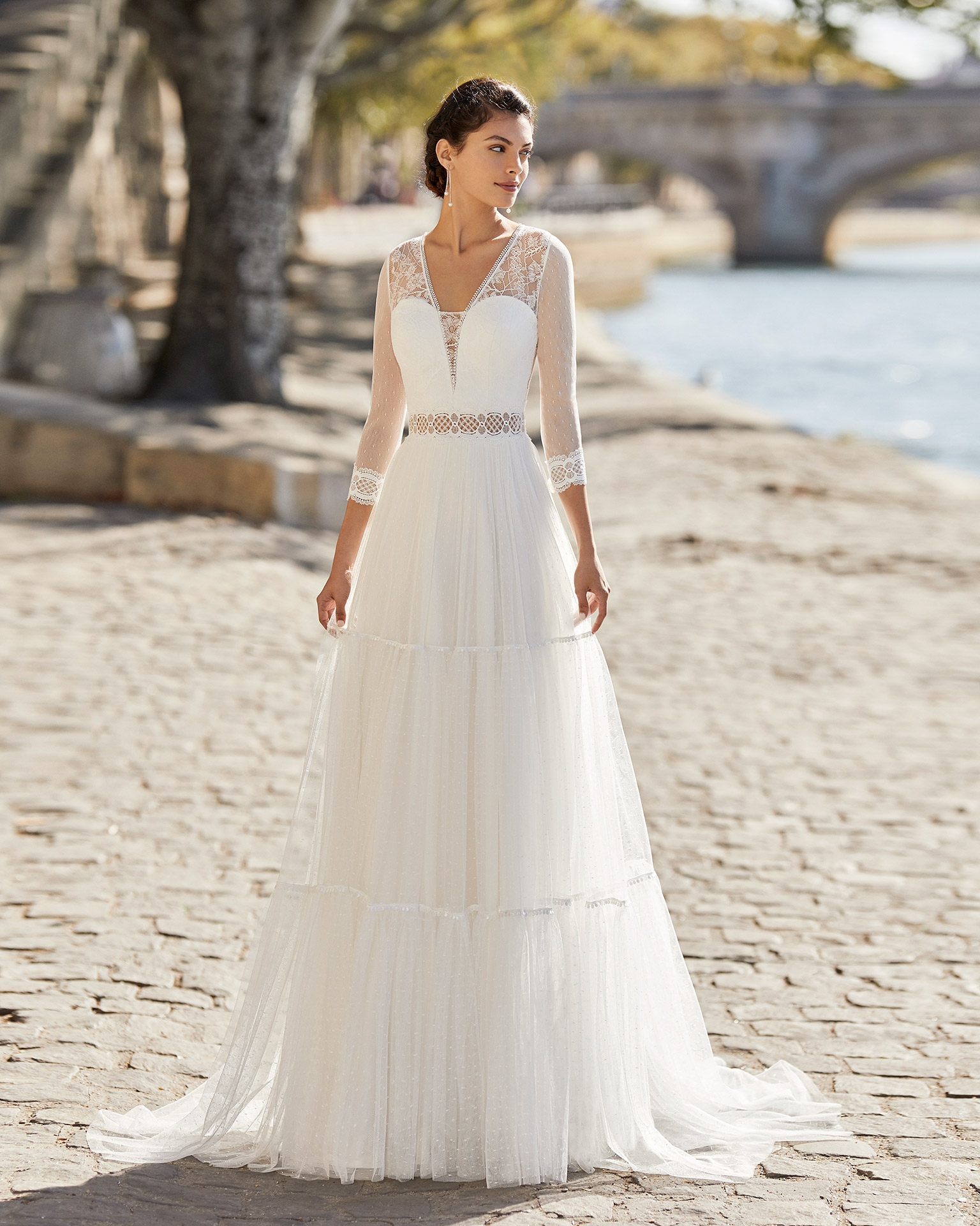 Wedding dress in dot tulle. V-neckline, three-quarter sleeves in dot tulle with lace trim and closed back in lace with buttons. 2021 ALMANOVIA Collection.
