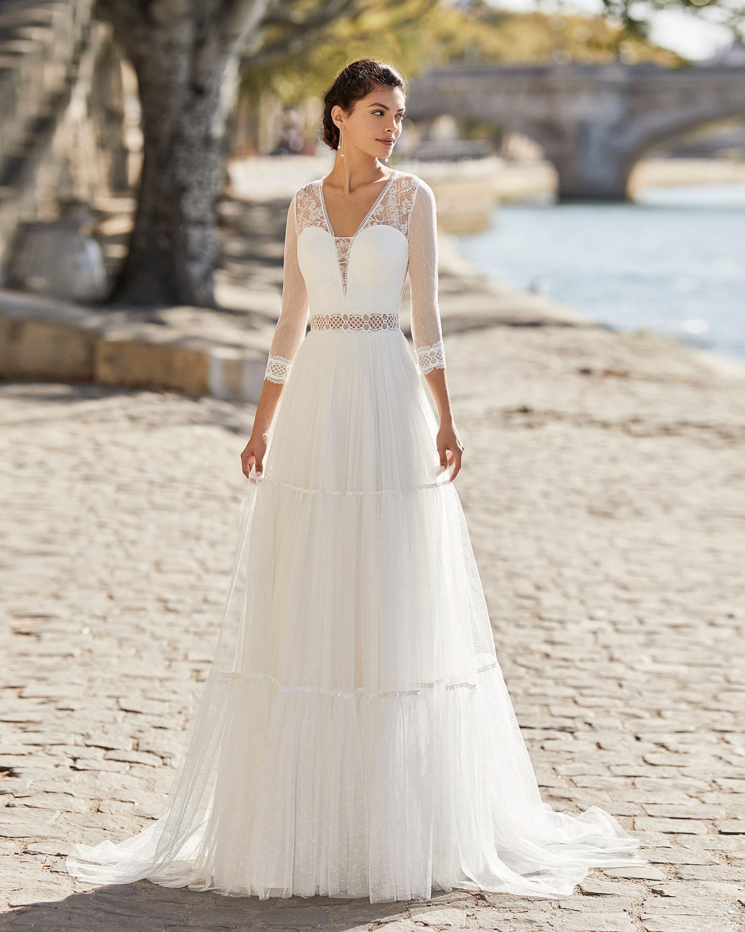 Vestido de novia de tul plumeti. Escote en V, mangas tres cuartos de tul plumeti y acabados en encaje y espalda cerrada de encaje y botones. Colección ALMANOVIA 2021.