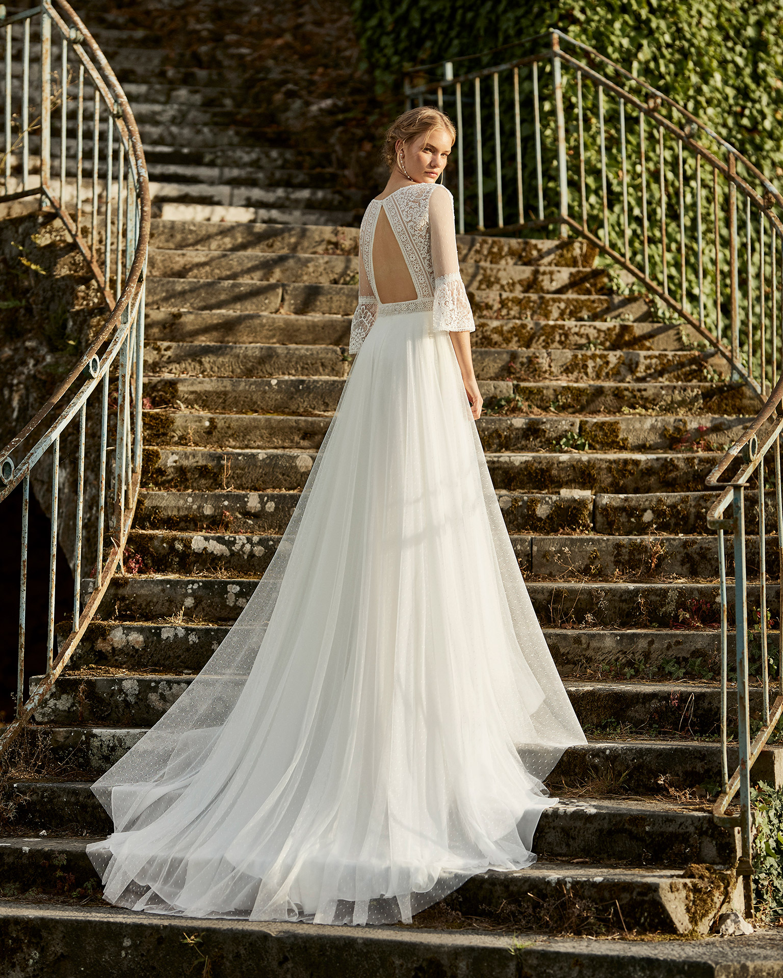 Wedding dress in dot tulle. V-neckline in lace, three-quarter-sleeves with flared cuffs in dot tulle and lace, and low back. 2021 ALMANOVIA Collection.