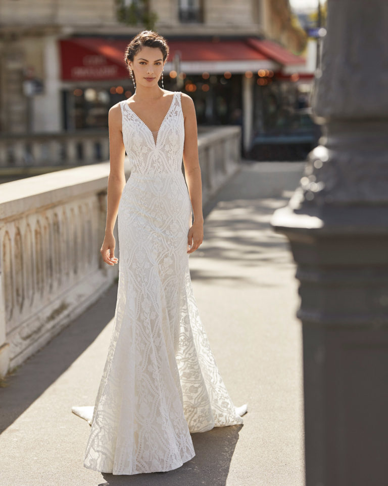 Vestido de novia de encaje rebrodé. Escote en V, tirantes y espalda escotada en forma de lágrima. Colección ALMANOVIA 2021.