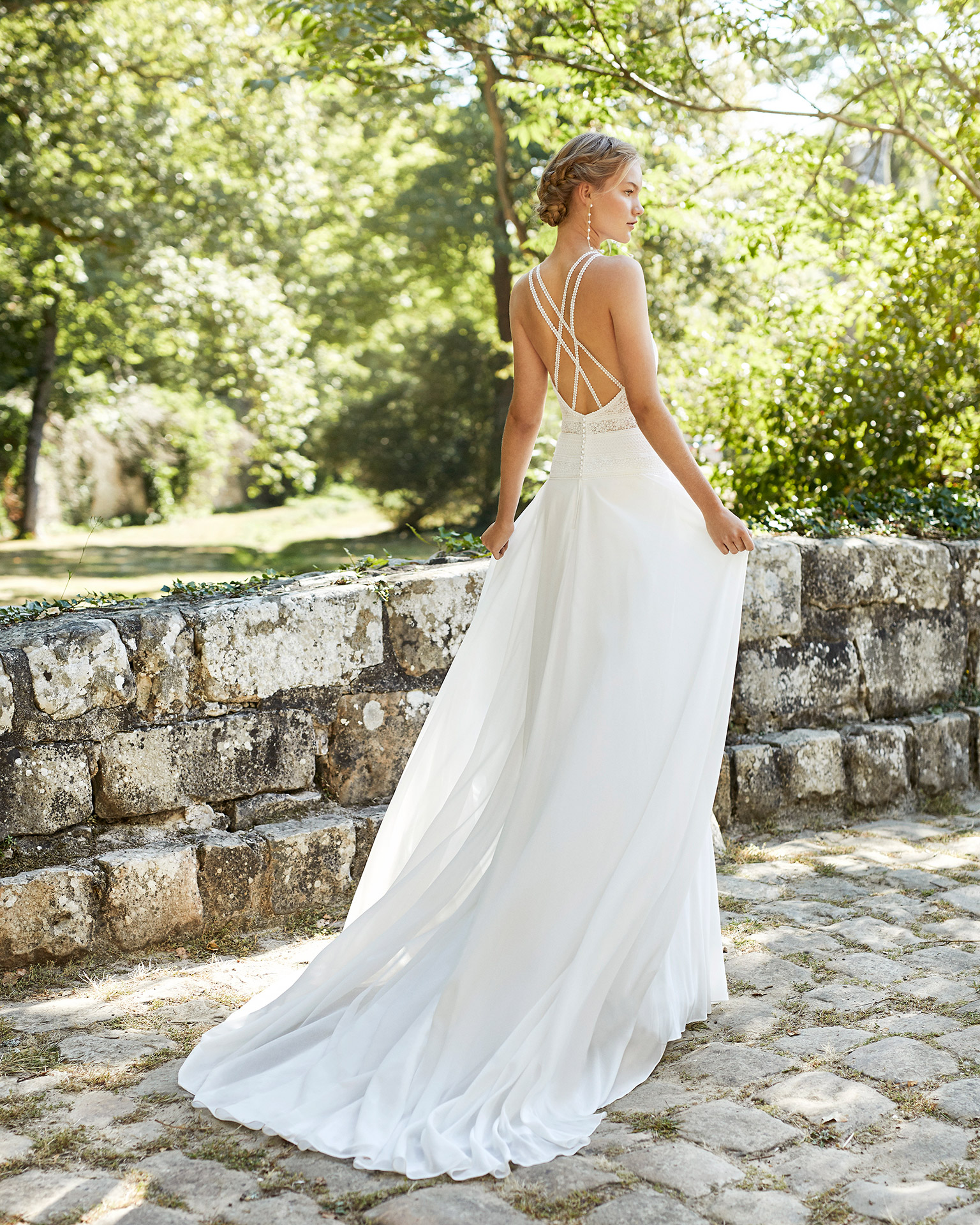 Wedding dress in chiffon. Closed neckline in lace, with shoulder straps and low back with crossover shoulder straps. 2021 ALMANOVIA Collection.