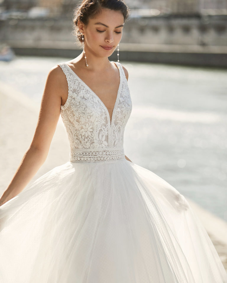 Wedding dress in dot tulle. V-neckline in beaded lace and low back with shoulder straps. 2021 ALMANOVIA Collection.