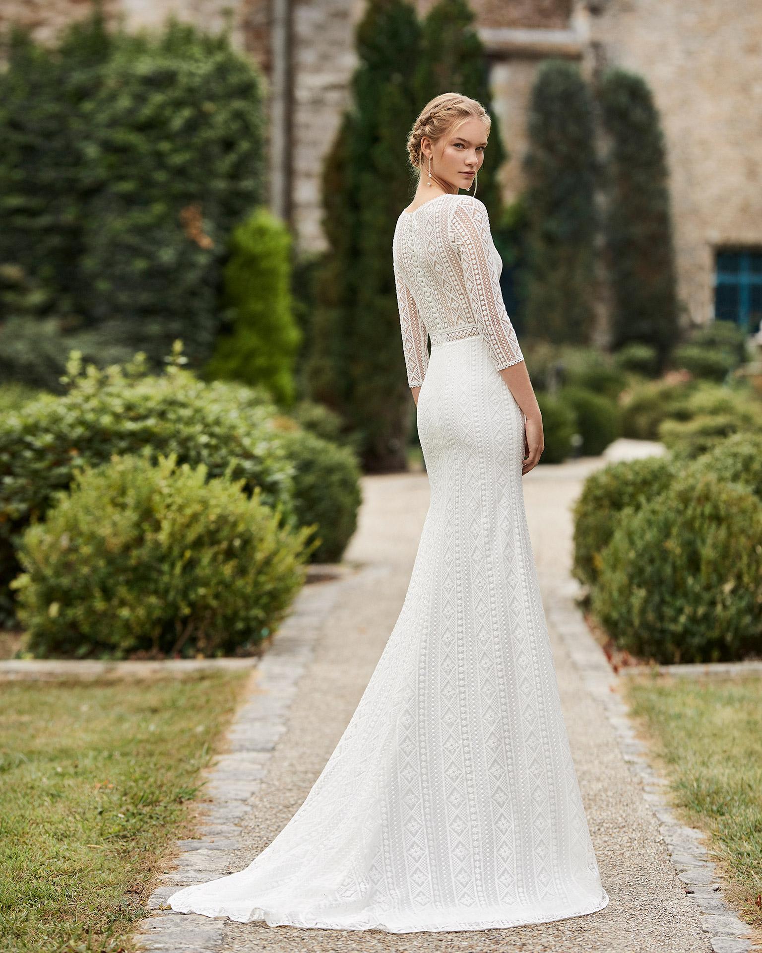 Vestido de novia de encaje. Escote en V, manga tres cuartos de encaje, cinturón de encaje y pedrería y espalda cerrada de encaje. Colección ALMANOVIA 2021.