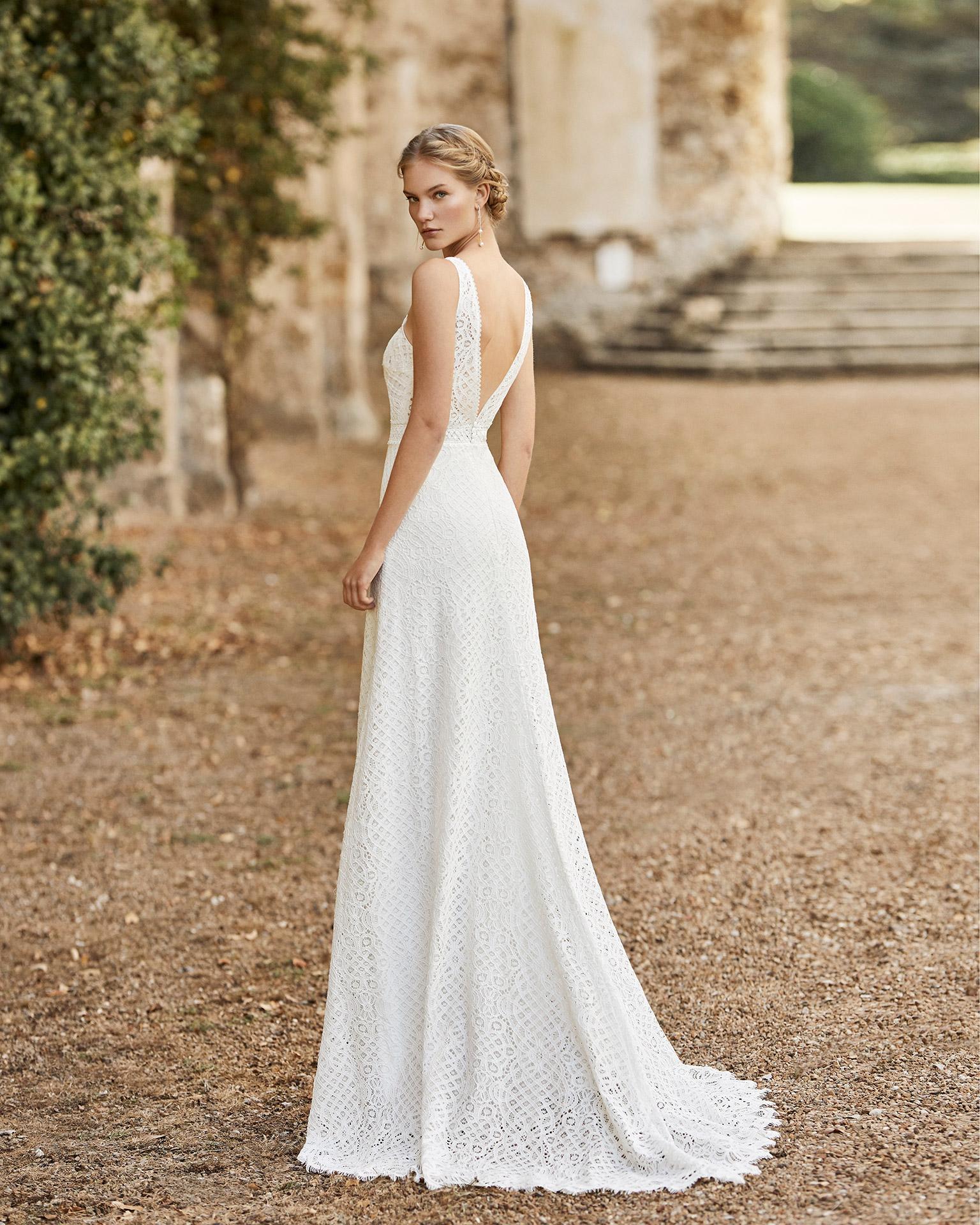 Vestido de novia de encaje. Escote y espalda en V, cinturón de encaje y pedrería y tirantes. Colección ALMANOVIA 2021.