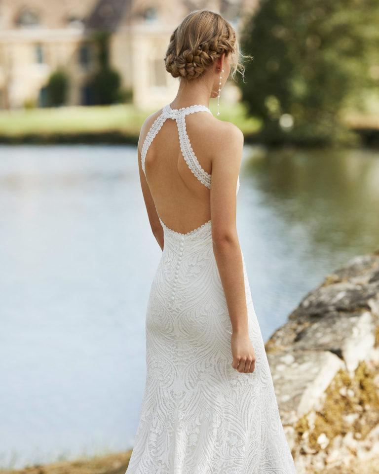 Vestido de novia de encaje. Escote halter y espalda escotada con dos tirantes que se abrochan en el cuello. Colección ALMANOVIA 2021.
