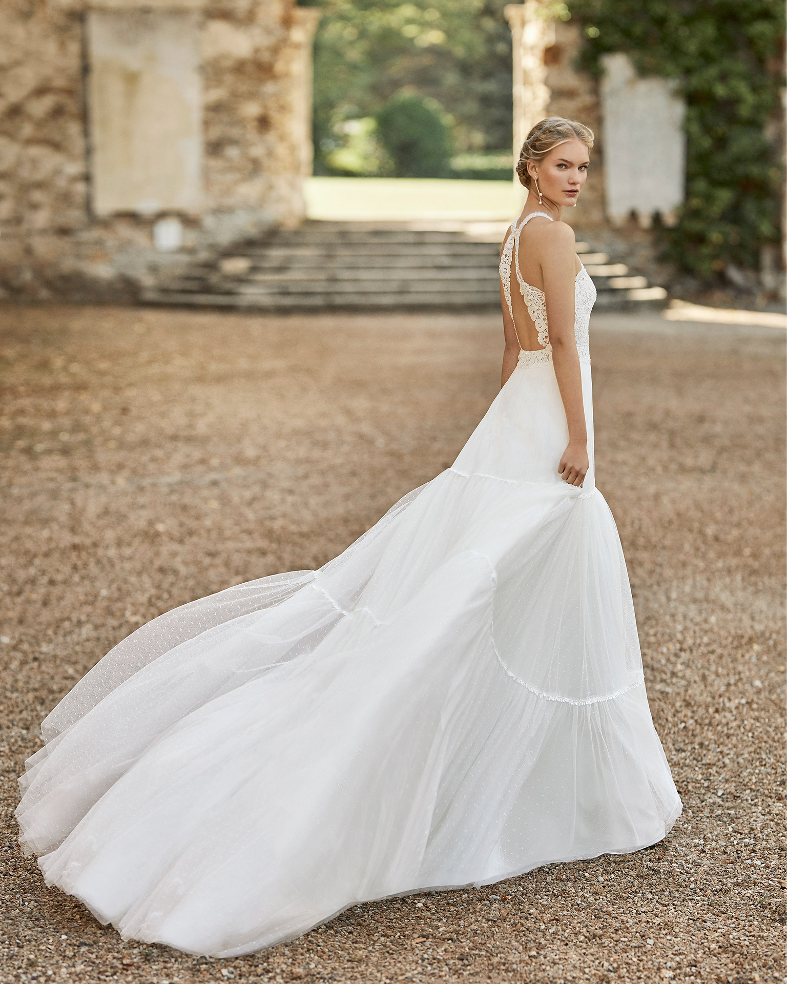 Wedding dress in dot tulle and lace. Halter neckline in beaded lace, lace belt and low back and lace shoulder straps attached to collar. 2021 ALMANOVIA Collection.