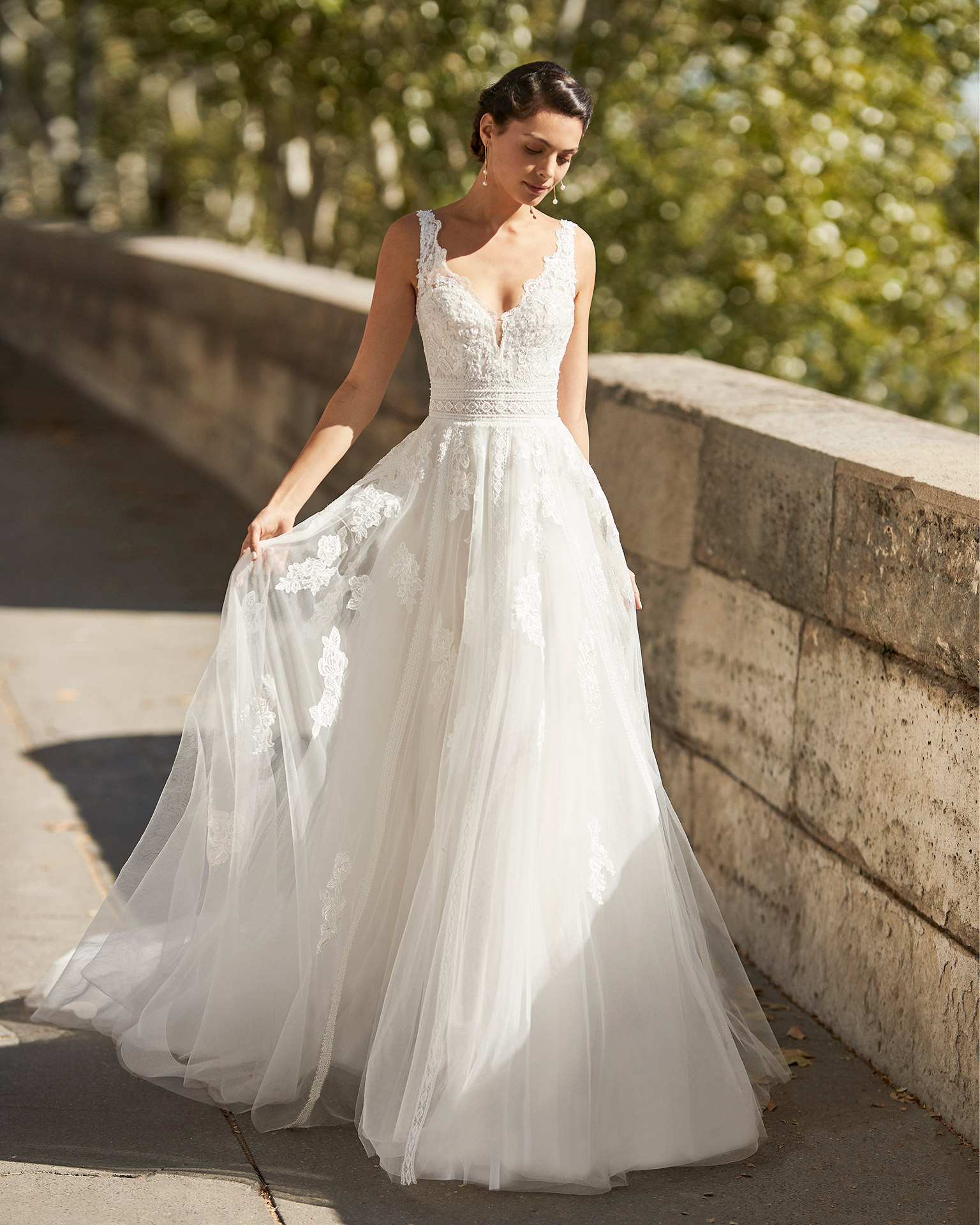 Wedding dress in tulle with lace appliqués on skirt. V-neckline in lace, beaded shoulder straps and belt and V-back in lace. 2021 ALMANOVIA Collection.