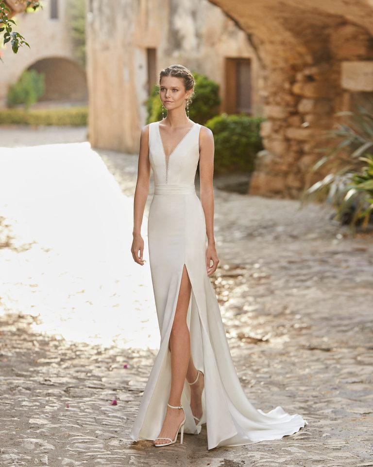 Boho-chic sheath-style wedding dress with front slit in skirt; with a bateau neckline and closed back with dot tulle. Unique Alma Novia model in crepe. 2022 ALMANOVIA Collection.